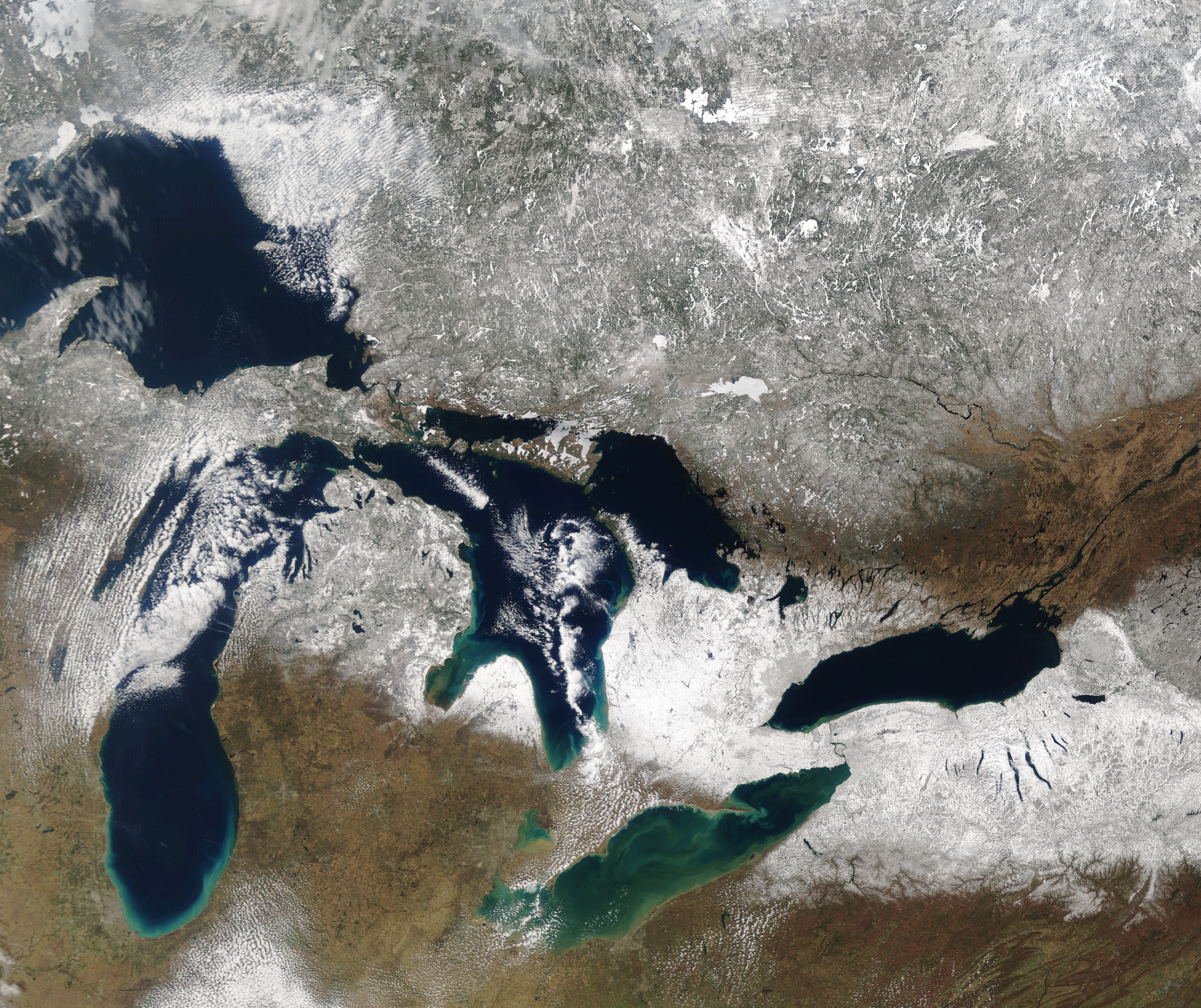 The swath of snow through the Great Lakes from last weekend is easily viewed from space in this image captured by satellite about noon Tuesday. (NASA MODIS image)