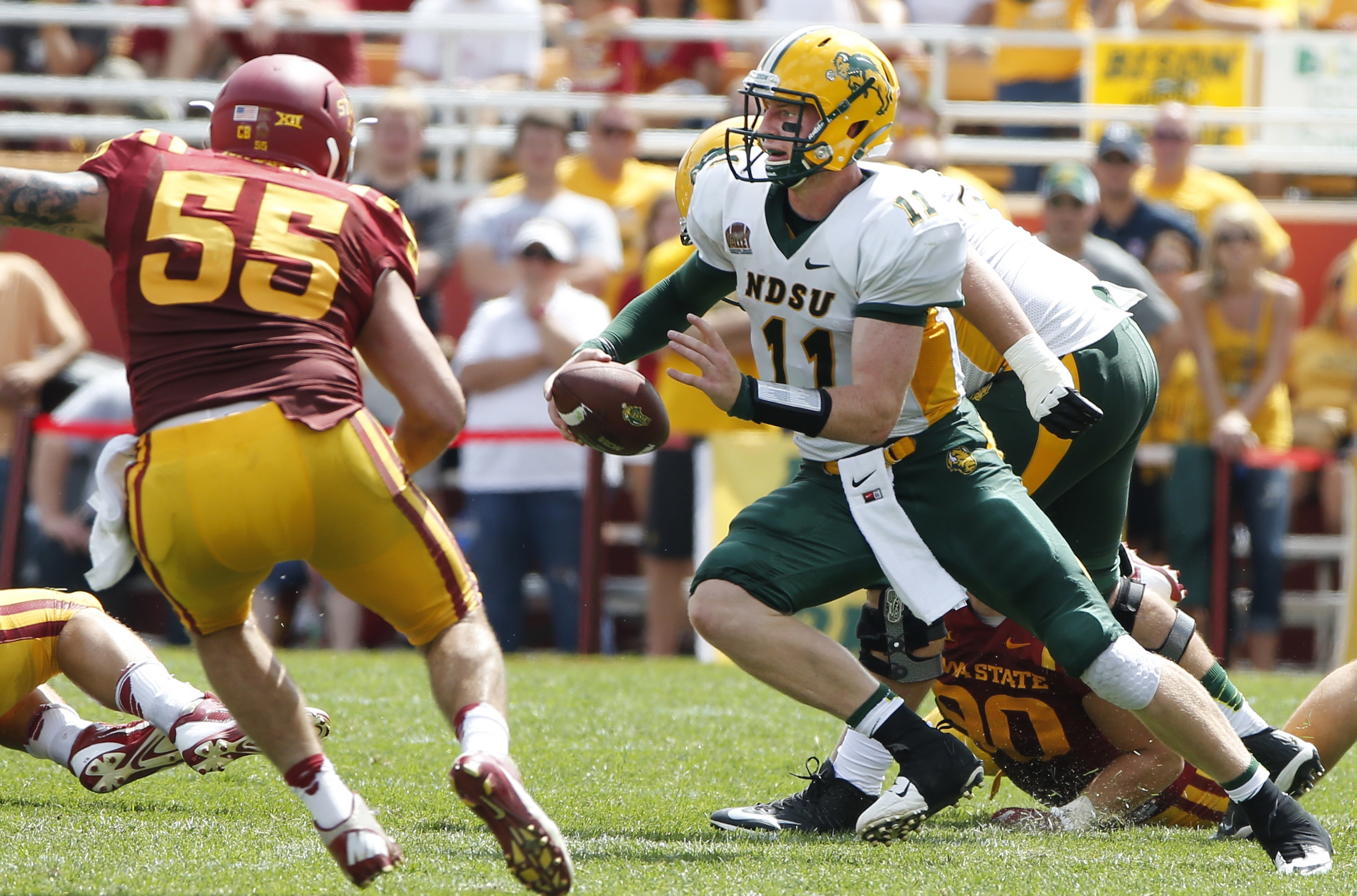 AMES, IA - AUGUST 30: quarterback Carson Wentz #11 of the North Dakota State Bison scrambles under pressure from linebacker Jevohn Miller #55 of the Iowa State Cyclones in the second half of play at Jack Trice Stadium on August 30, 2014 in Ames, Iowa. North Dakota State defeated Iowa State 34-14. (Photo by David Purdy/Getty Images)