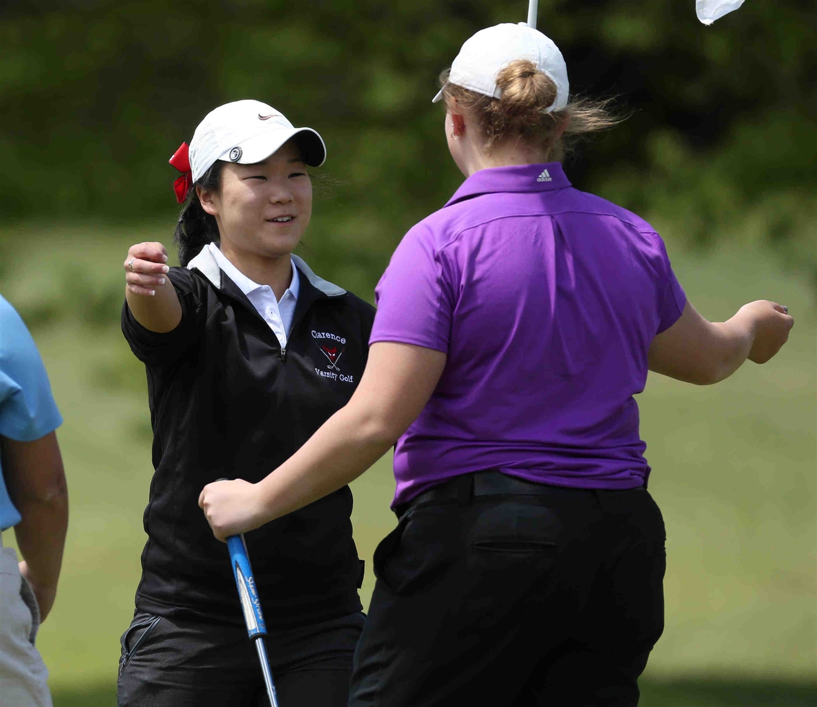 Clarence's Alexis Kim, left, accepts a congratulatory hug from Southwestern's Marissa DelMonaco after winning the Section VI girls golf championship Wednesday at Gowanda Country Club. (James P. McCoy/Buffalo News)