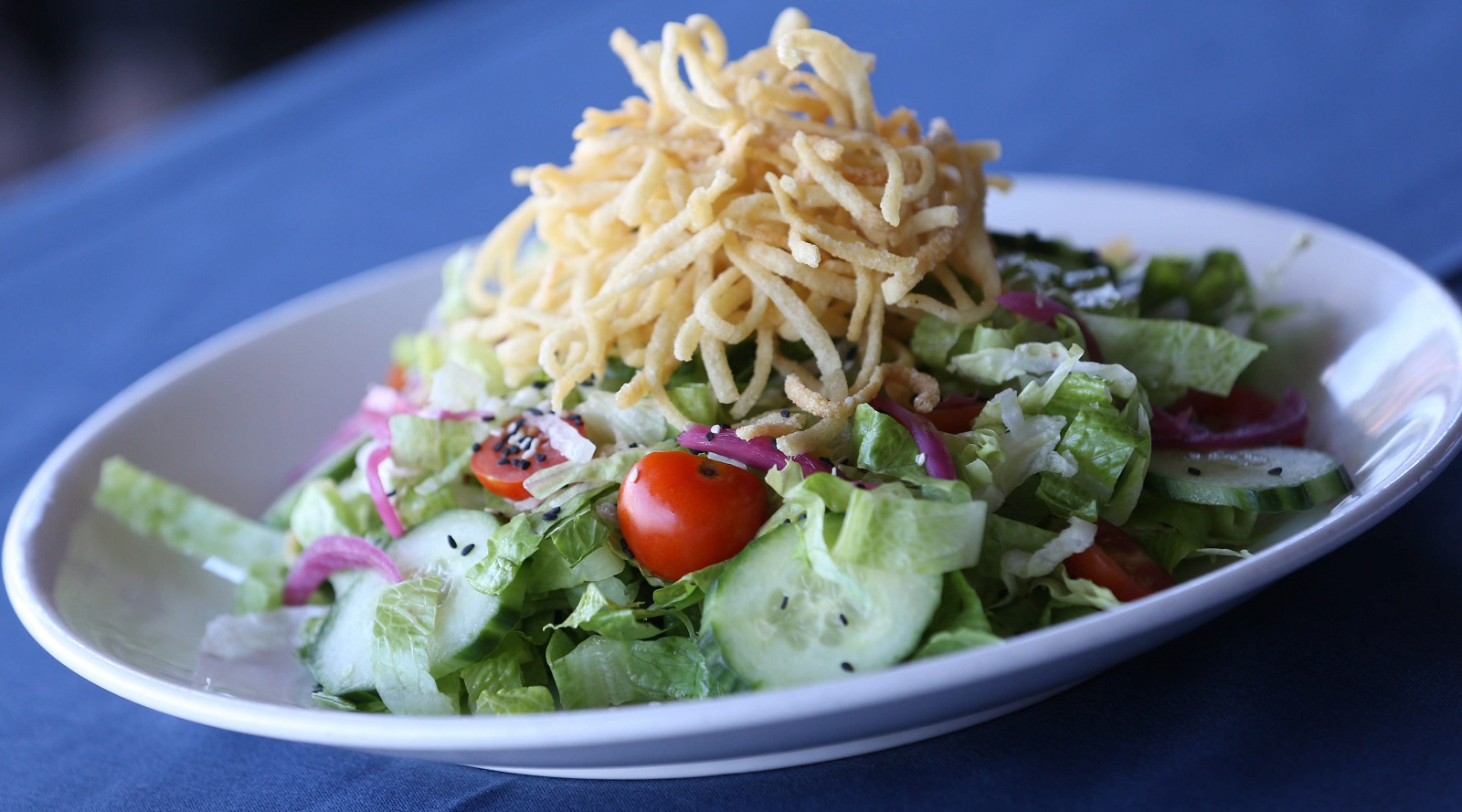 The Asian chopped salad is made with romaine, iceberg, tomato, cucumber, pickled red onion, sesame seeds and fried noodles. (Sharon Cantillon/Buffalo News)