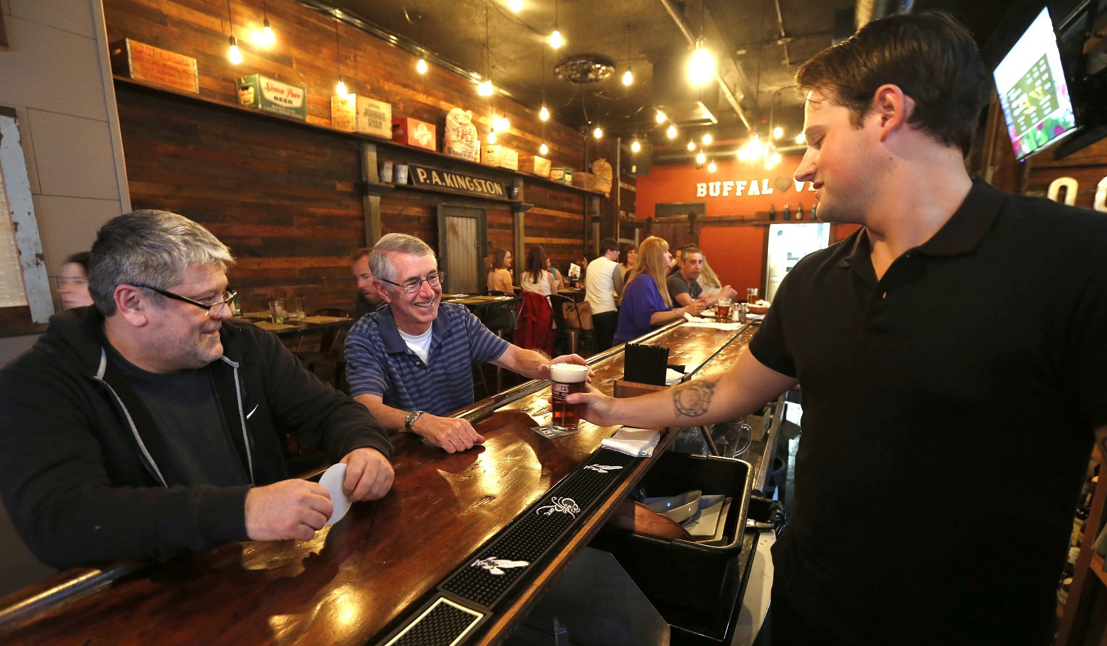 Patrons Alan DePounceau, of Buffalo, left, and Chris Kennedy, center, of the Town of Tonawanda grab a couple of pints from bartender Jordan Schmidt, right, at Local Kitchen & Beer Bar. (Robert Kirkham/Buffalo News)