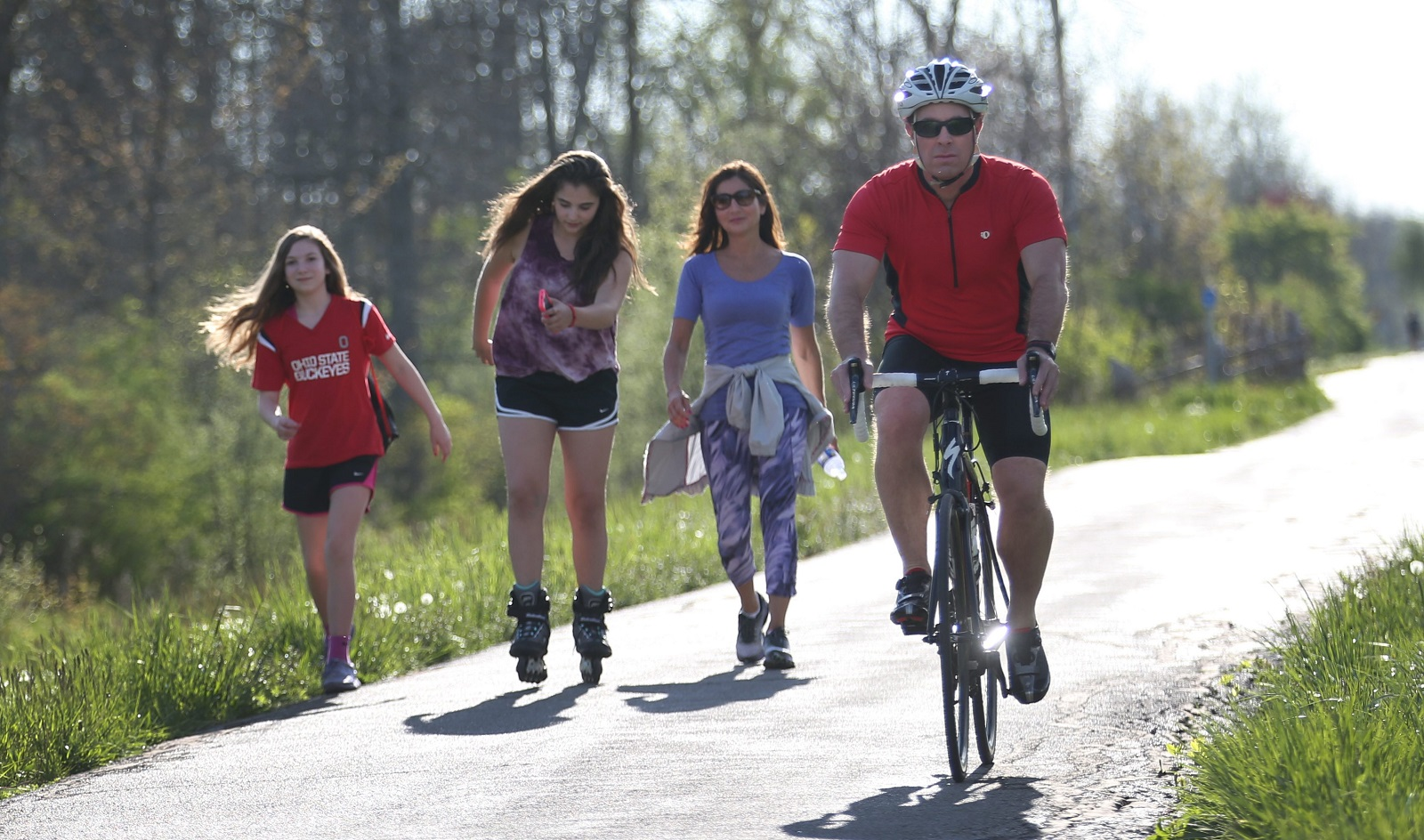 Dr. Marc Fineberg, right, shares part of the Clarence bike path Wednesday with Ella Petrulla, 11, left, her friend Eva Nuchereno, 11, and her friend's mother Norine Nuchereno. (Sharon Cantillon/Buffalo News)