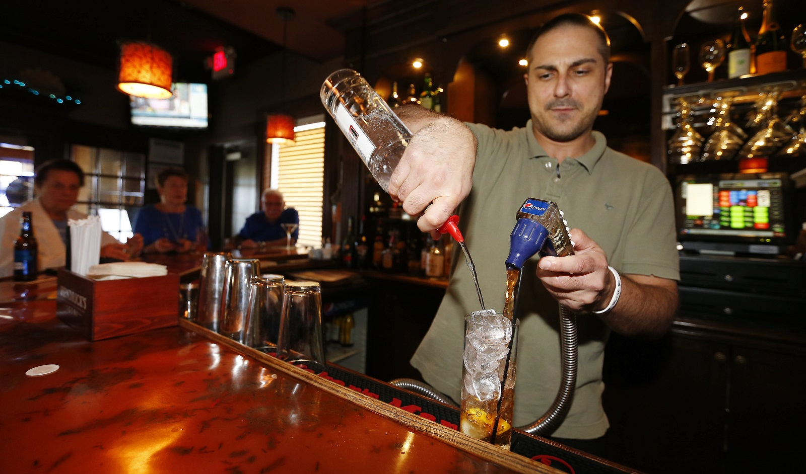 Bartender Frank Damon pours a drink at the WaterStone Grill in Hamburg. (Mark Mulville/Buffalo News)
