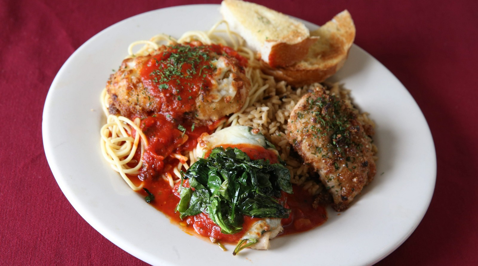 A combination of chicken Florentine, chicken Parmigiana and pecan crusted chicken over a bed of pasta, from Lombardi's. (Sharon Cantillon/Buffalo News)