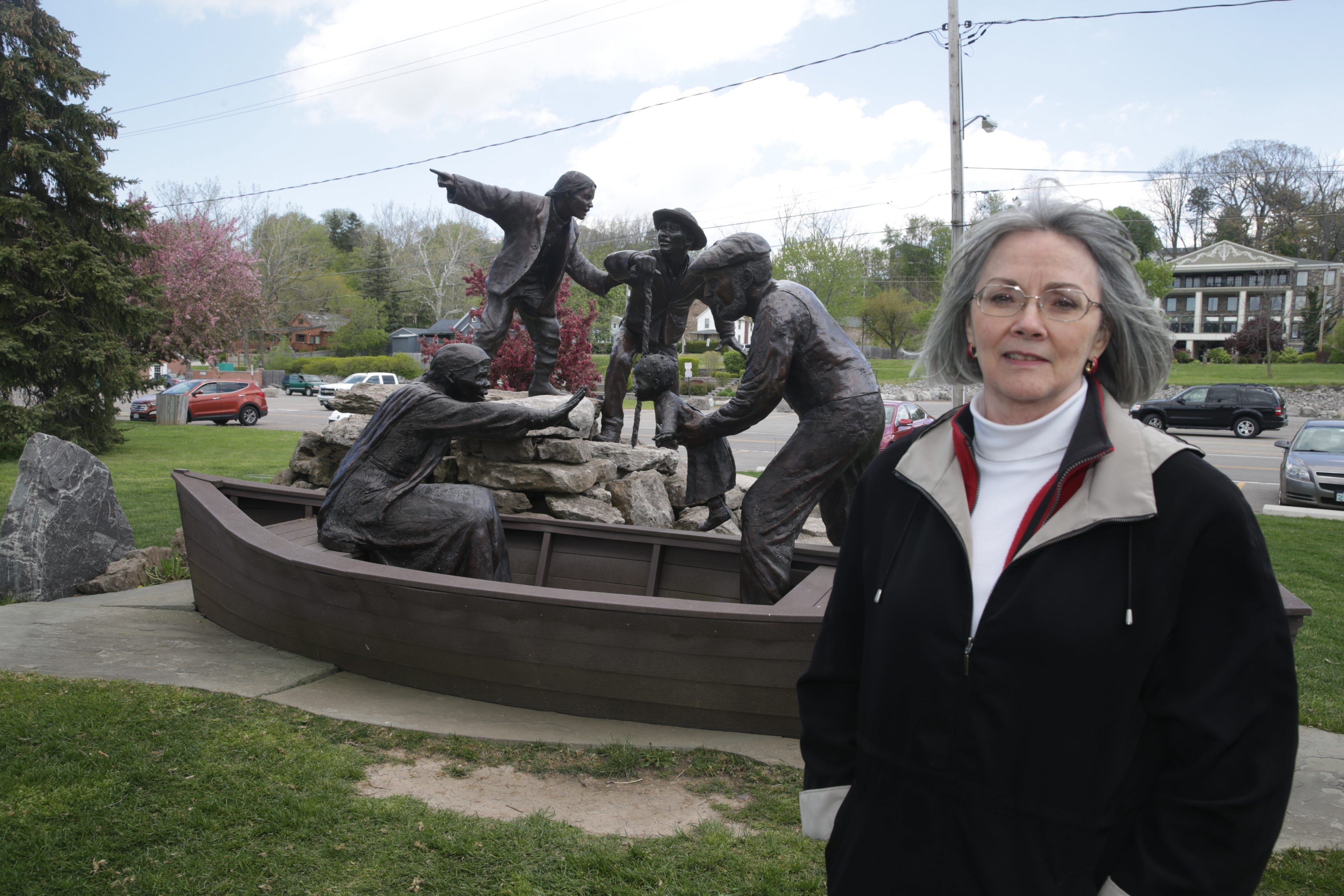 """Pamela Hauth, Historical Association of Lewiston museum curator, visits the """"Freedom Crossing"""" monument at foot of Center and Water streets. Words referring to abolitionists Harriet Tubman and Josiah Tryon are inscribed on the statue."""