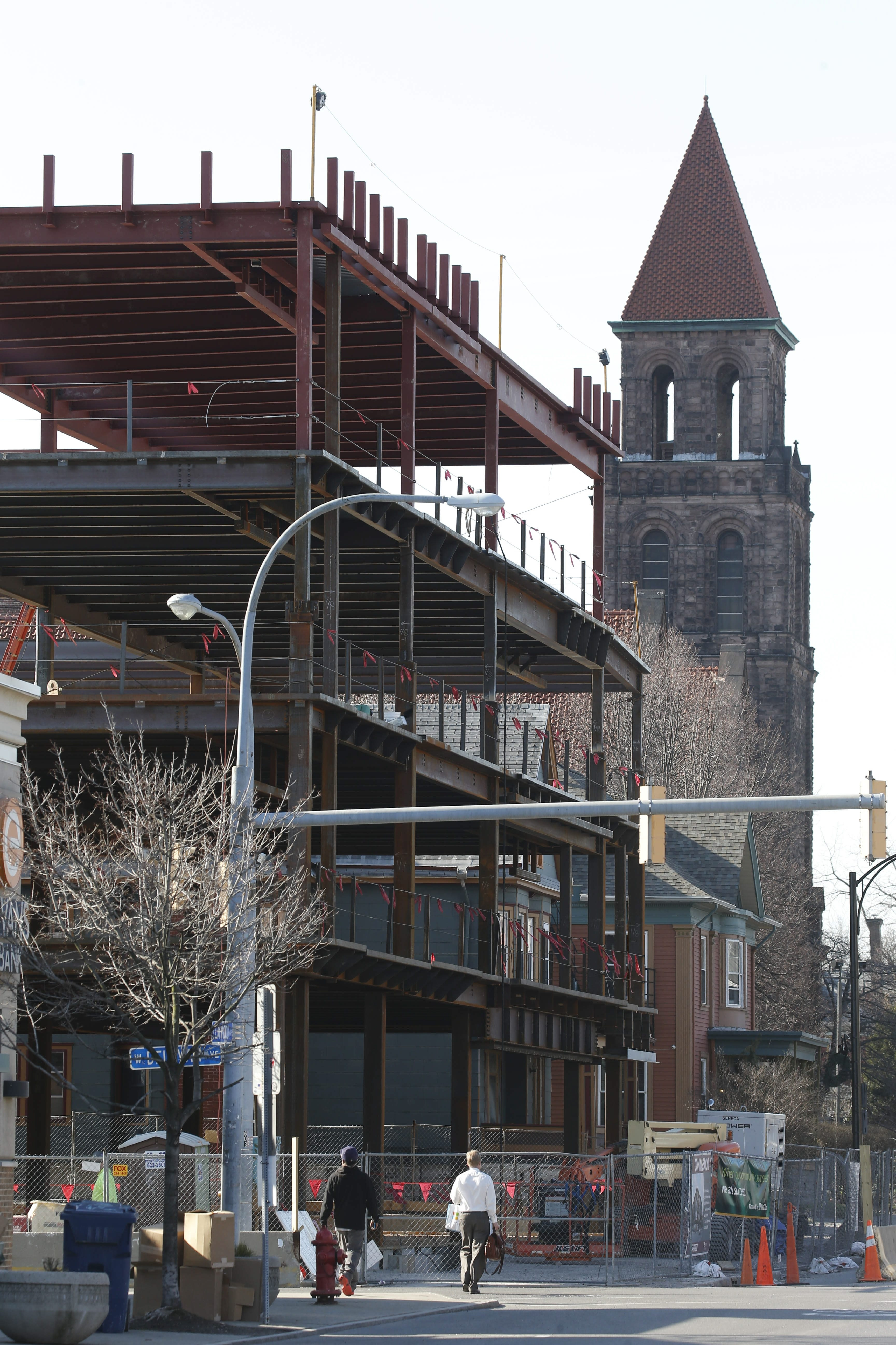 The steel frame of a new, mixed-use structure at the corner of Elmwood and West Delevan avenues rises in front of the steeple of the Lafayette Avenue Presbyterian Church, an icon of the Elmwood Village.