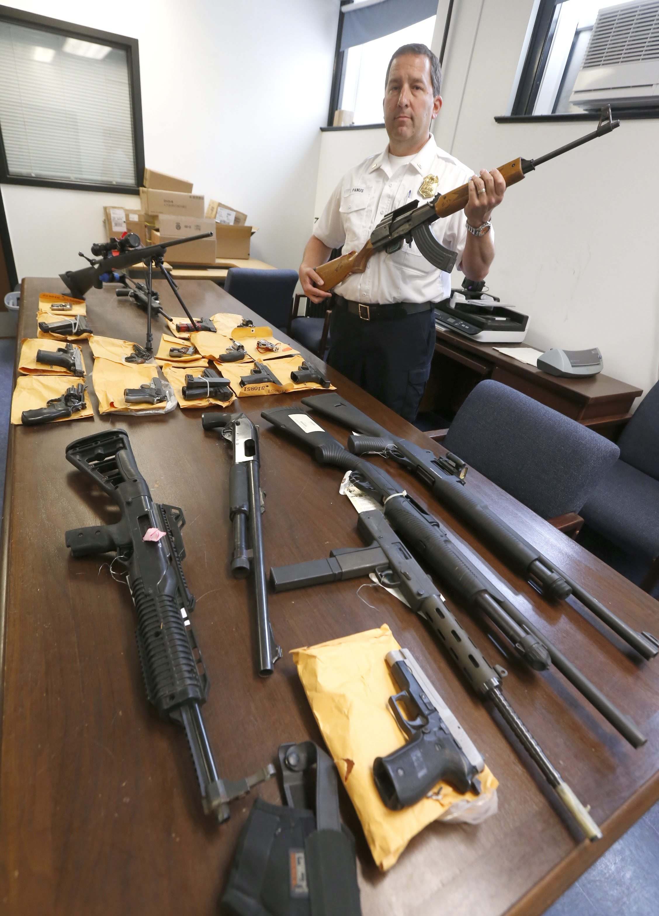 Buffalo Police Lt. Joe Panus shows a collection of confiscated guns that they've taken off the street including a semi-automatic AK-47 that he was holding in the basement of the police head quarters on Wednesday, May 25, 2016.  (Robert Kirkham/Buffalo News)