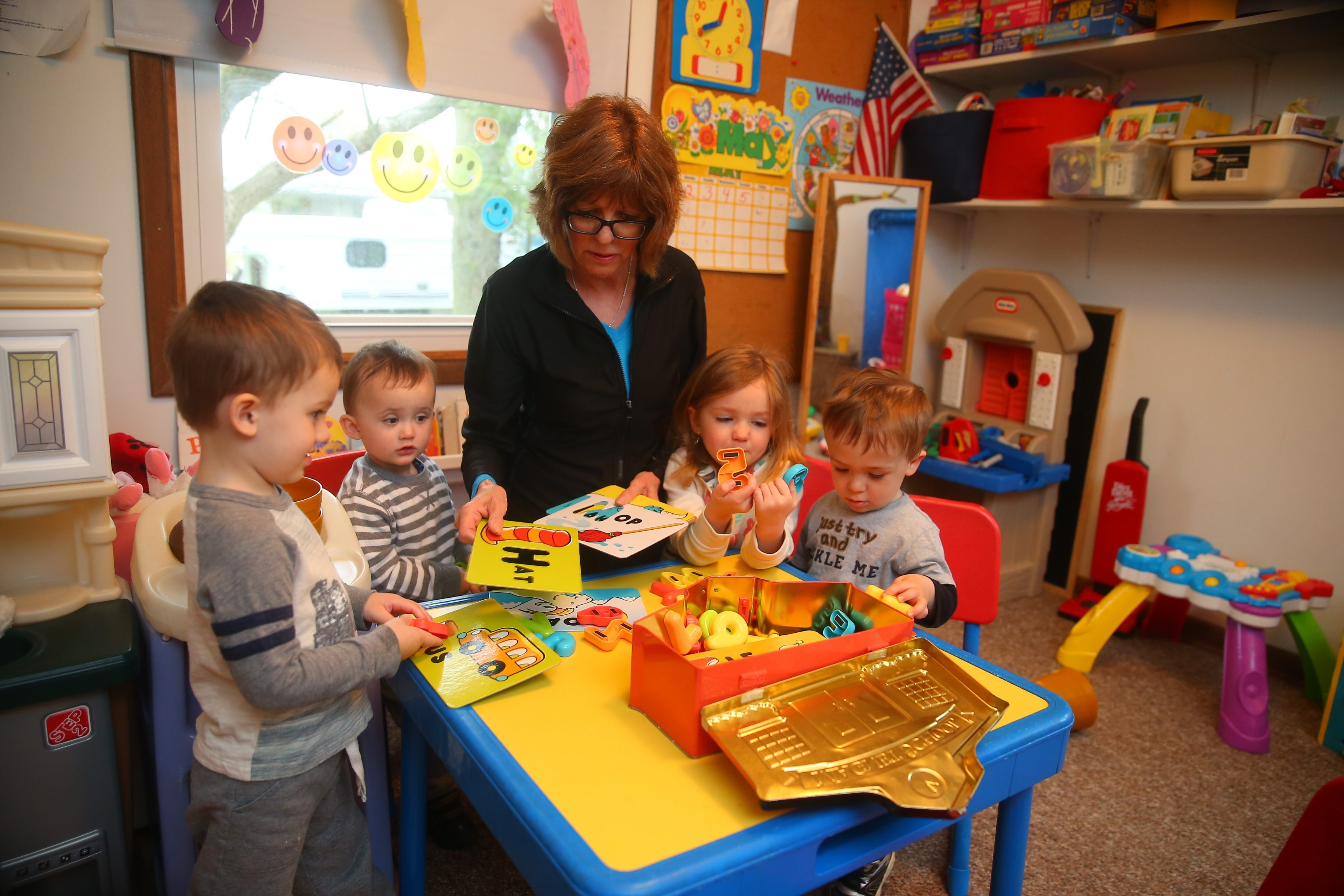 Mary Hausberger with, from left, Dominic Irizarry, 3, Ryan Wisniewski, 1½, Riley Jubulis, 5, and Joseph Pirrone, 1½. Hausberger has been operating a day care center out of her house in West Seneca for more than 20 years.