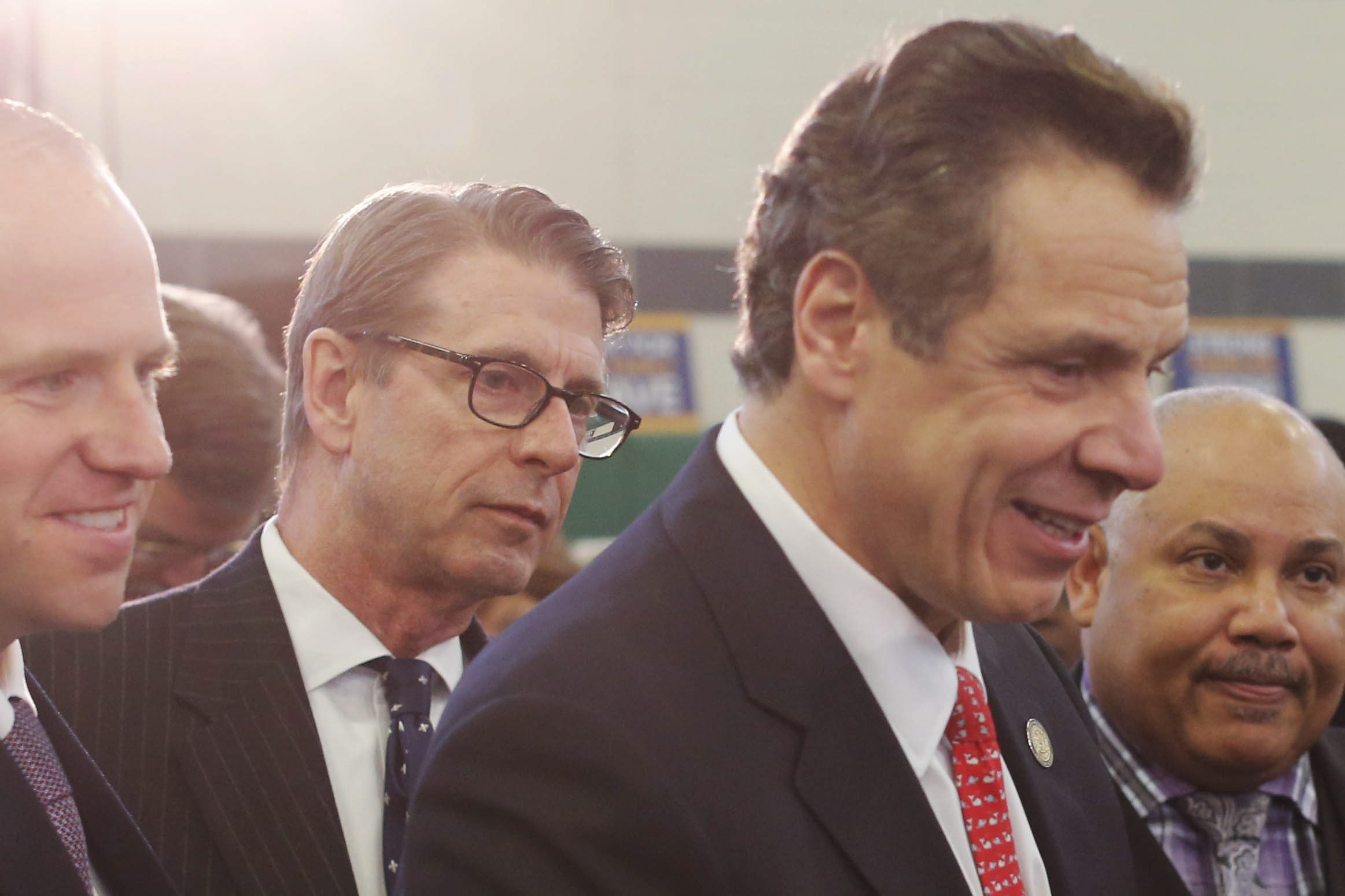 Peter Cutler, left, working as an aide to New York Gov. Andrew Cuomo, right, stands at the governor's side as he mingles with dignitaries following an event to promote paid family leave at the Delevan-Grider Community Center in Buffalo on Feb. 17. (Derek Gee/News file photo)