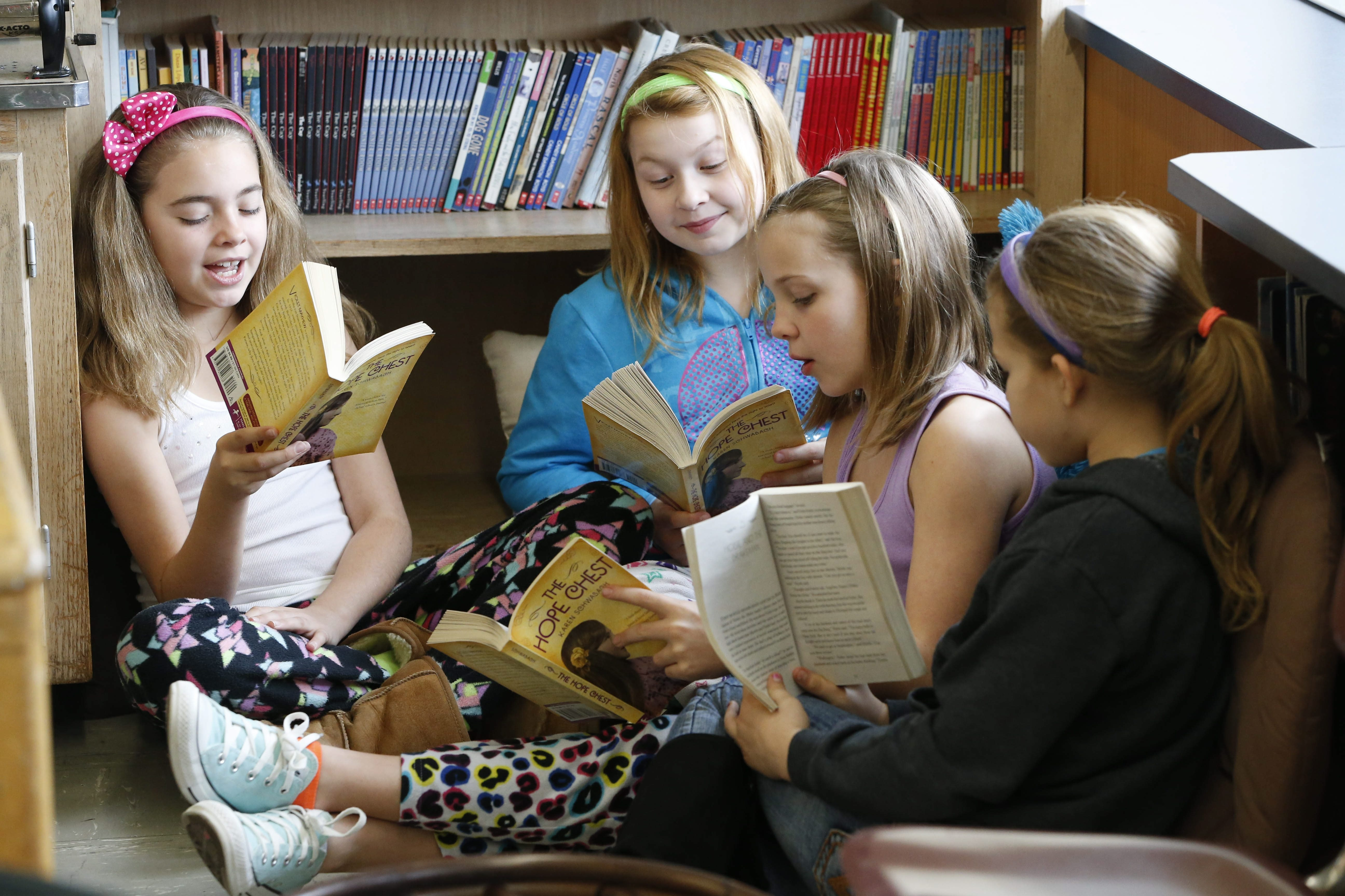 From left, Nora Jetter, Jasmine Root, Olivia Gibson and McKenna Eberle read together for a class assignment in Mrs. Bayer's fourth-grade class Friday at Alexander Hamilton Elementary School, which will soon close.