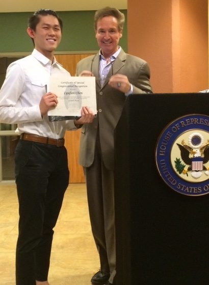 Rep. Brian Higgins congratulates Ricky Chen on his art achievement.