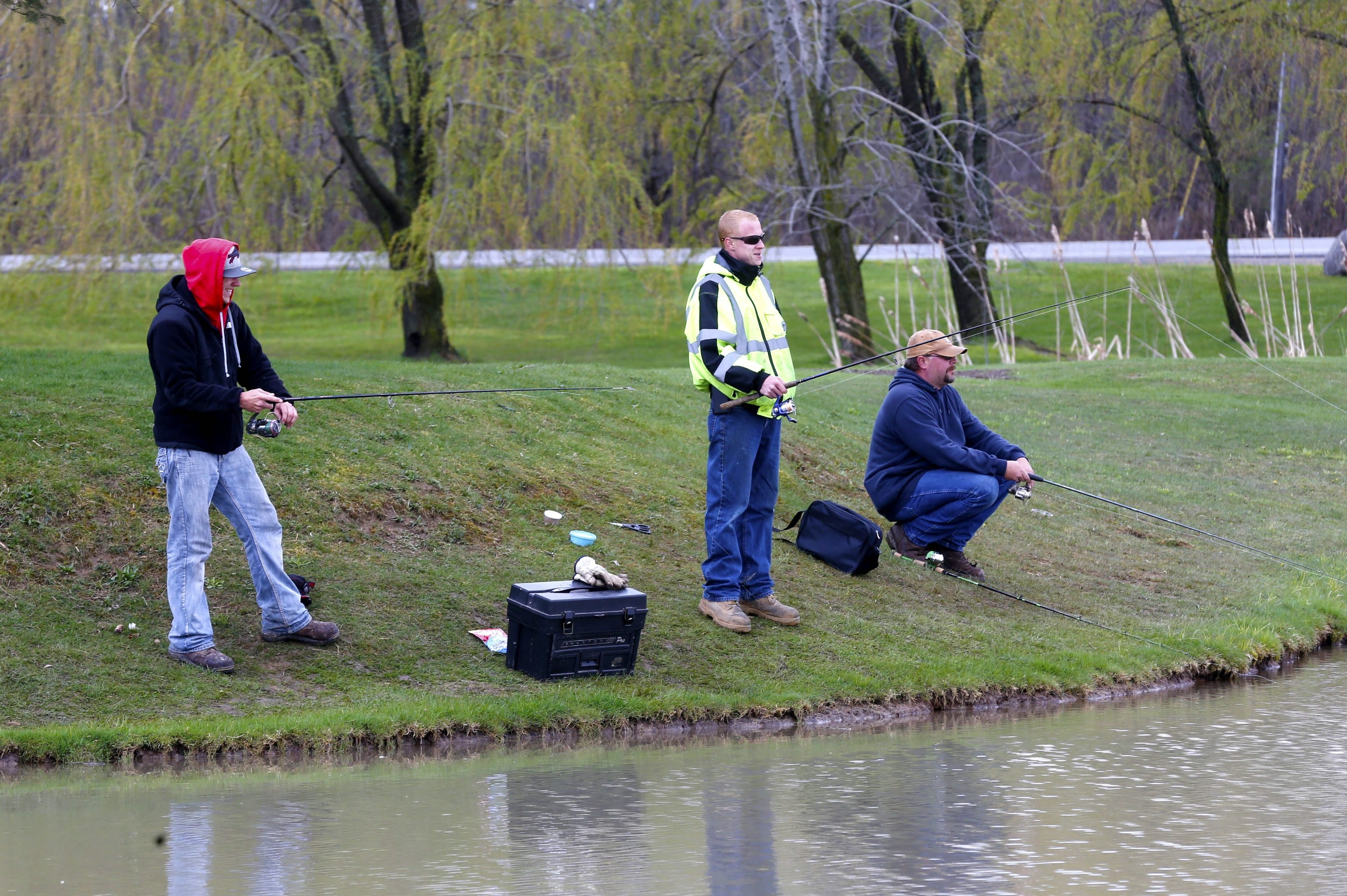 From left, brothers Mark and Cody Heuser of the Town of Tonawanda and friend Dennis King of North Tonawanda do a little fishing at the pond at Oppenheim Park on Niagara Falls Blvd. in Niagara Falls (Robert Kirkham/Buffalo News)