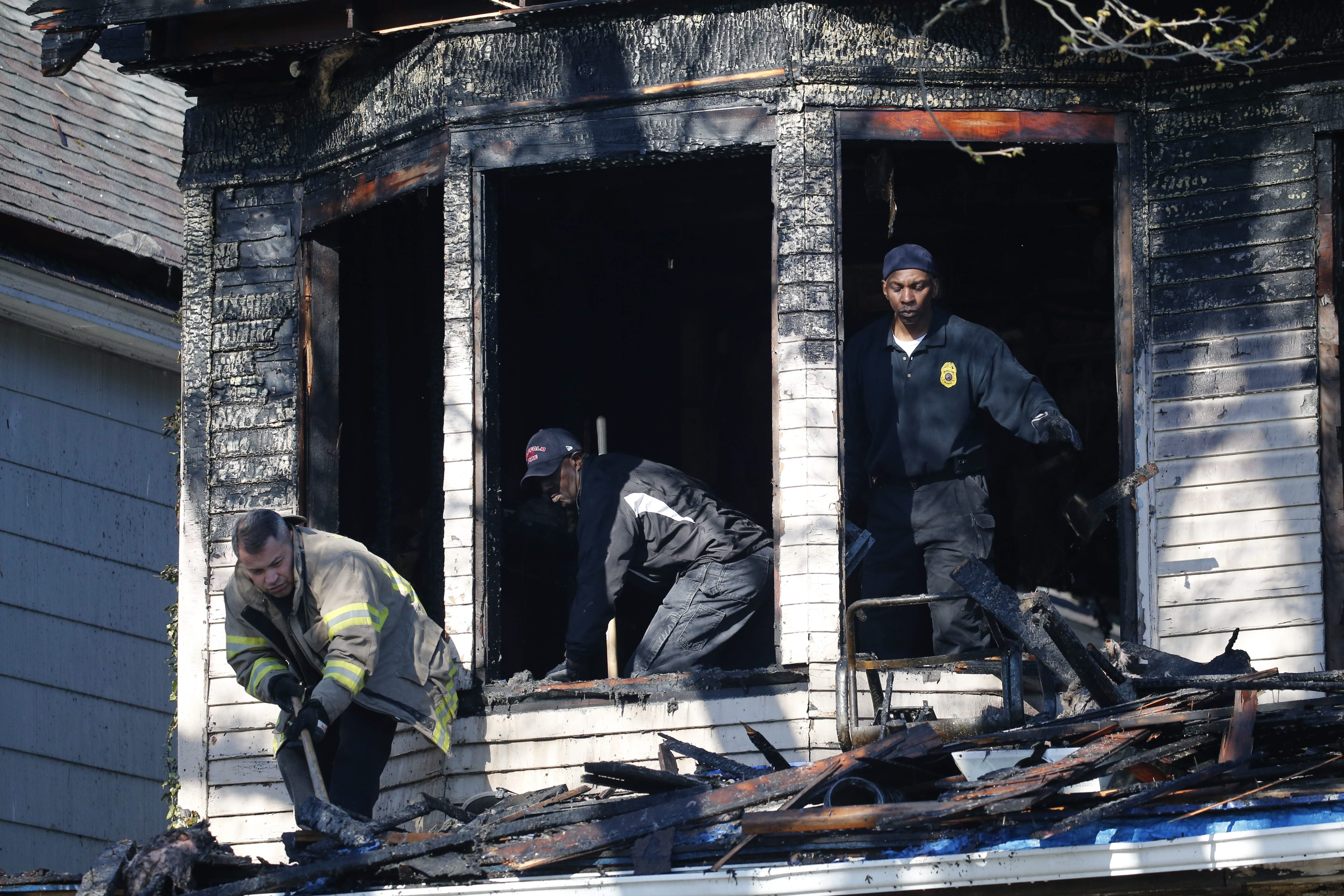 Buffalo fire marshals sift through the rubble of a home on Moselle Street where firefighters rescued a woman earlier Friday. (Derek Gee/Buffalo News)