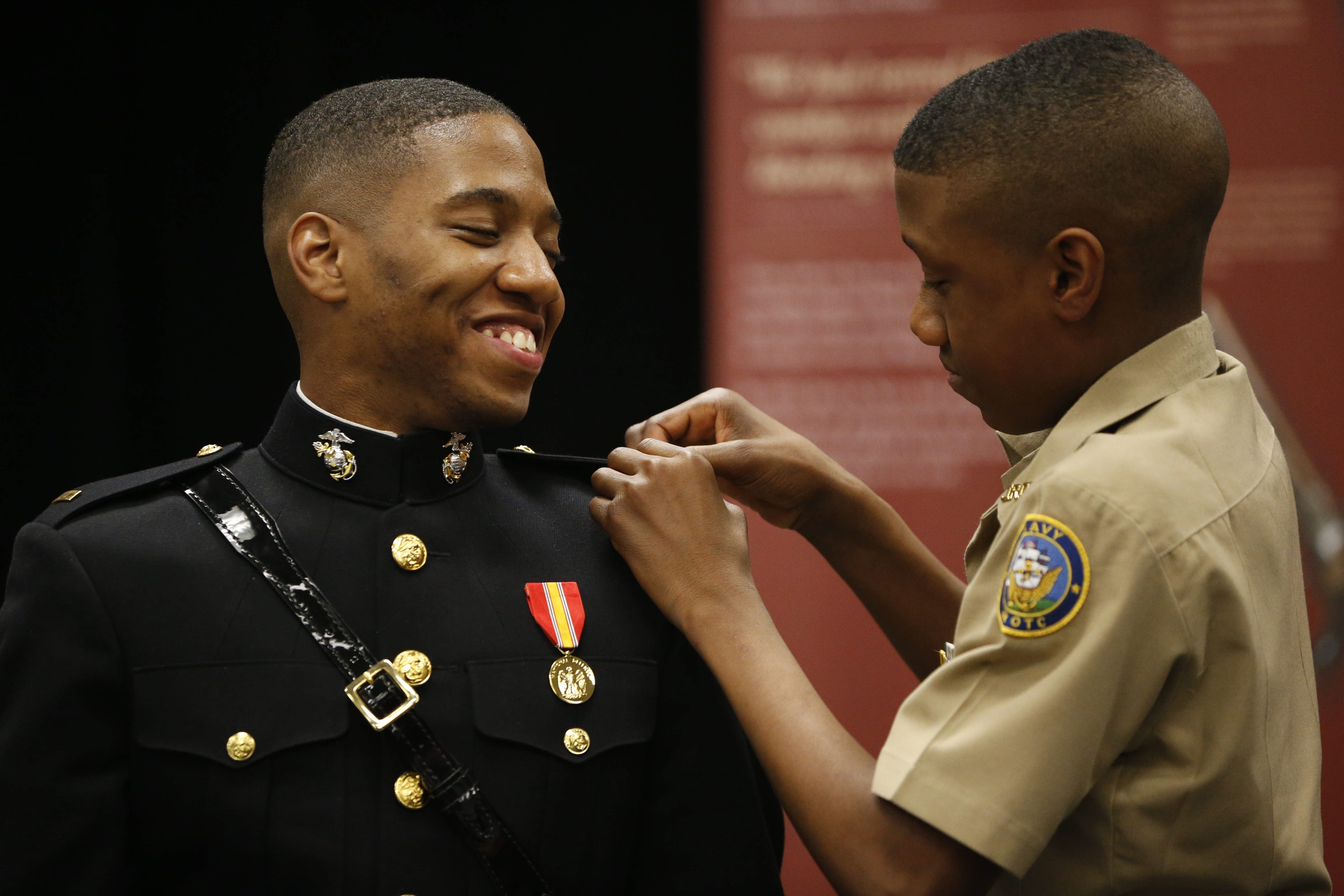 "U.S. Marine Corps Lt. Anthony J. Carter, a 2012 graduate of Maritime Charter School, laughs as his little brother Devon, 14, pins on his lieutenant bars during a ceremony at his alma mater on Wednesday.  ""I was heading down the wrong path, to become another statistic. If I had continued down that path, there's no way I would have graduated from high school and gone to college."" – U.S. Marine Corps Lt. Anthony J. Carter"
