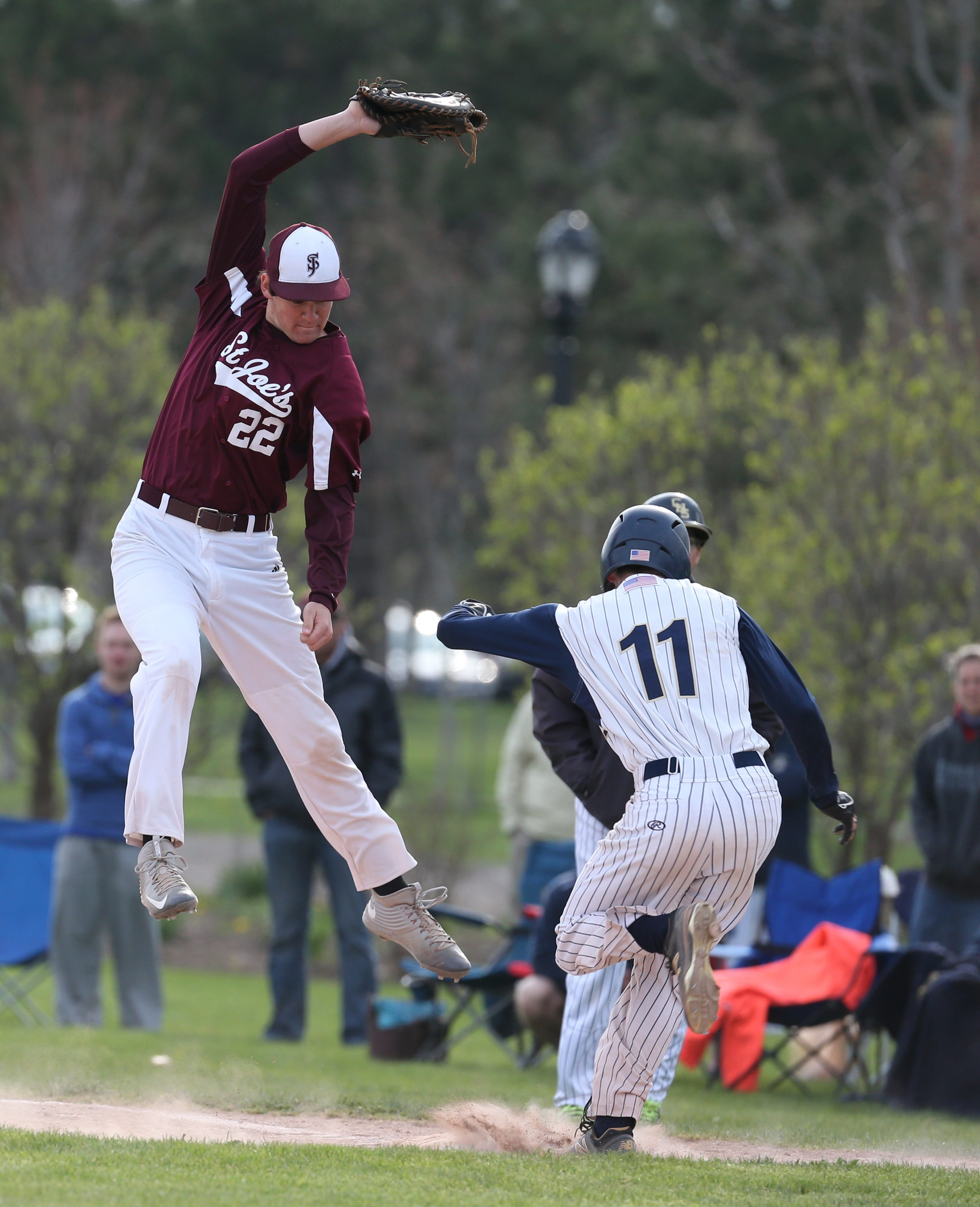 Canisius' Michael Gabriele beats out a single on St. Joe's first baseman Anthony Brophy. Both teams are ranked in the top 10.