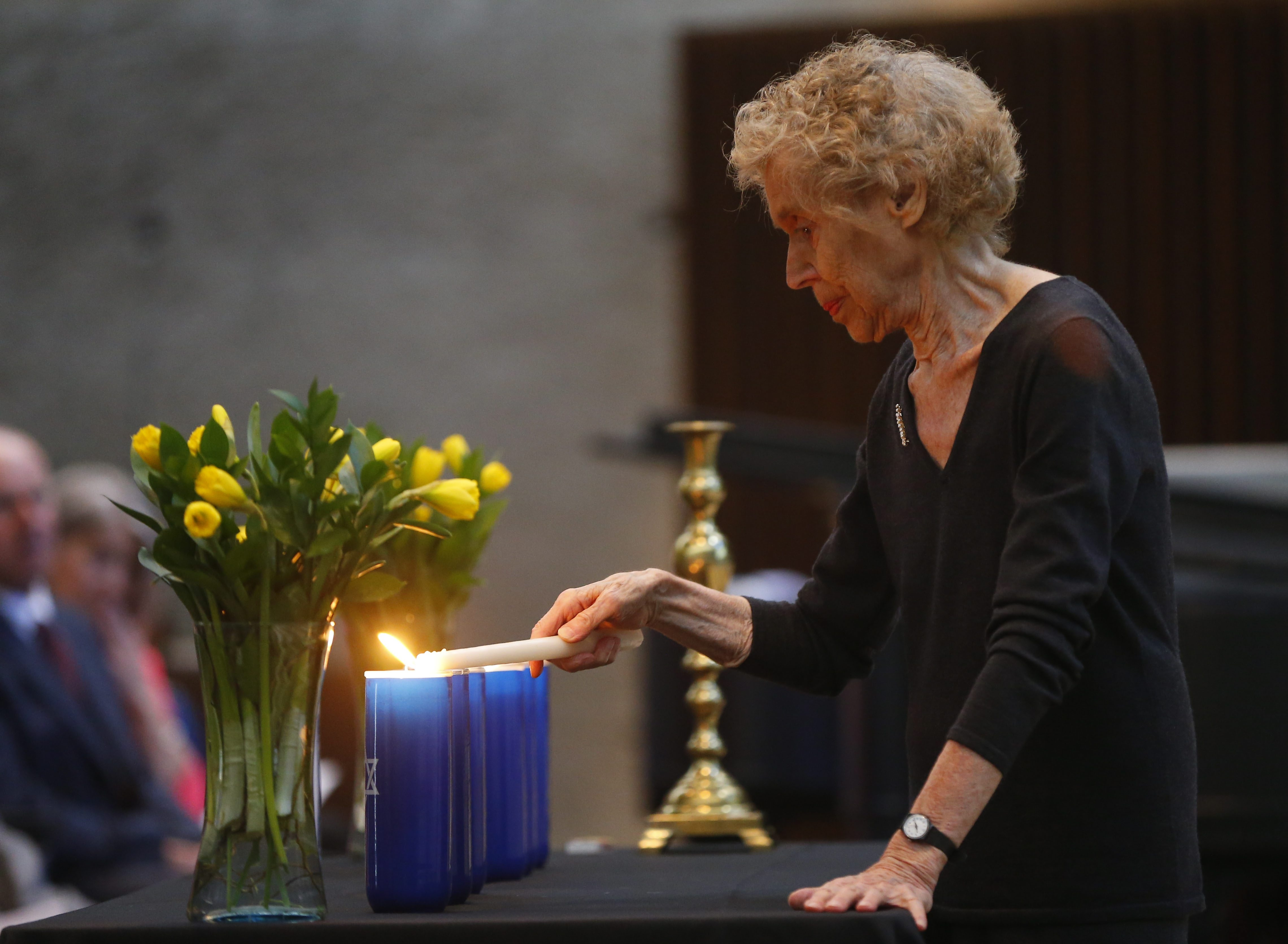 Holocaust survivor Sophia Veffer lights a remembrance candle at Temple Beth Zion on Sunday.