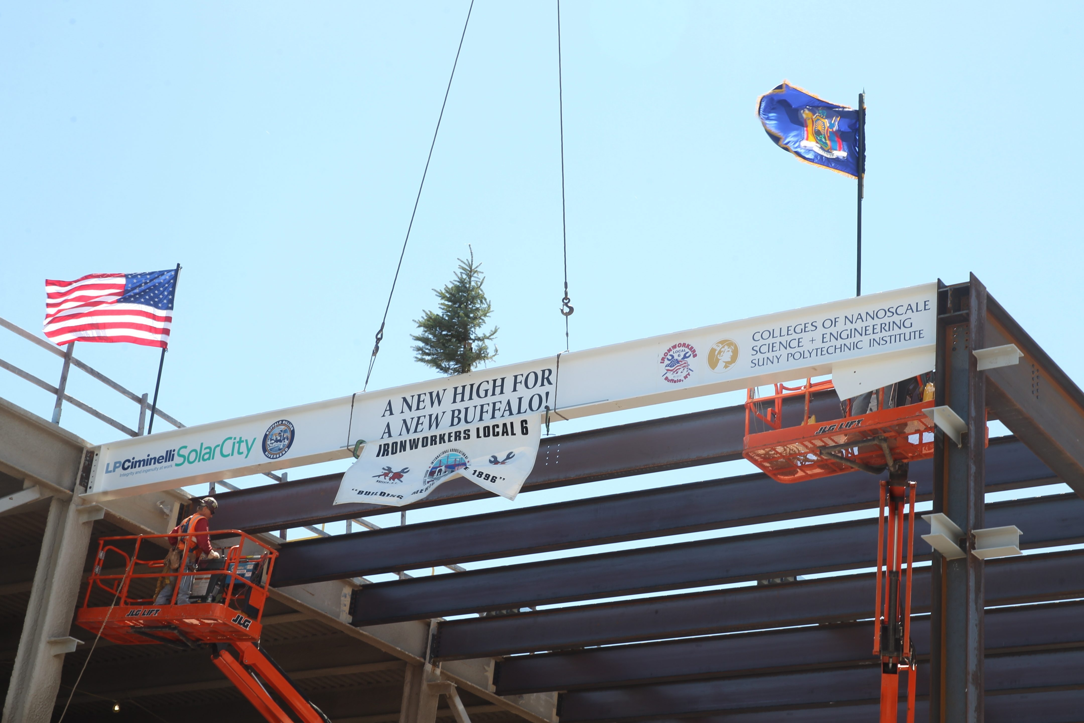 """""""A new high for a new Buffalo,"""" reads a banner flapping from the last beam placed during the topping-off ceremony at SolarCity in South Buffalo on Aug. 4. (John Hickey/News file photo)"""