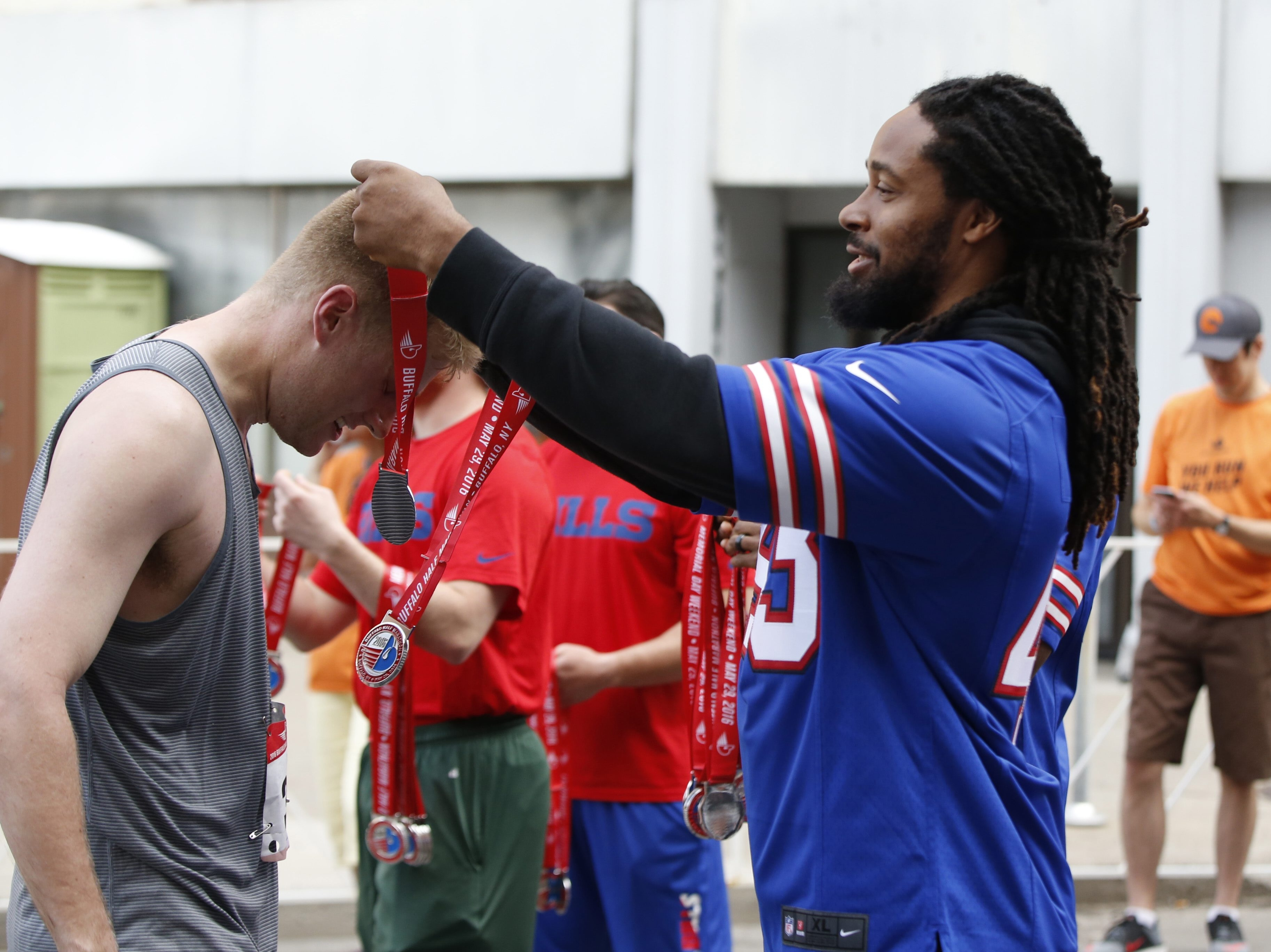 Phillip Thomas of the Bills presents a medal to one of the finishers of Sunday's Buffalo Marathon.
