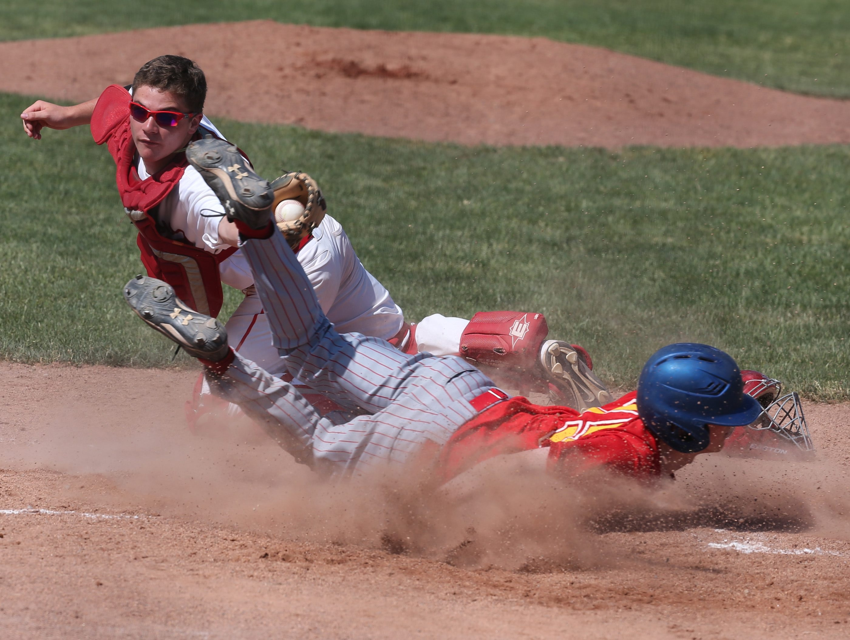 Williamsville East's Jack Rubins slides safely into home under the tag of Iroquois catcher Brent Reid during the Flames' three-run second inning in the Class A championship game.