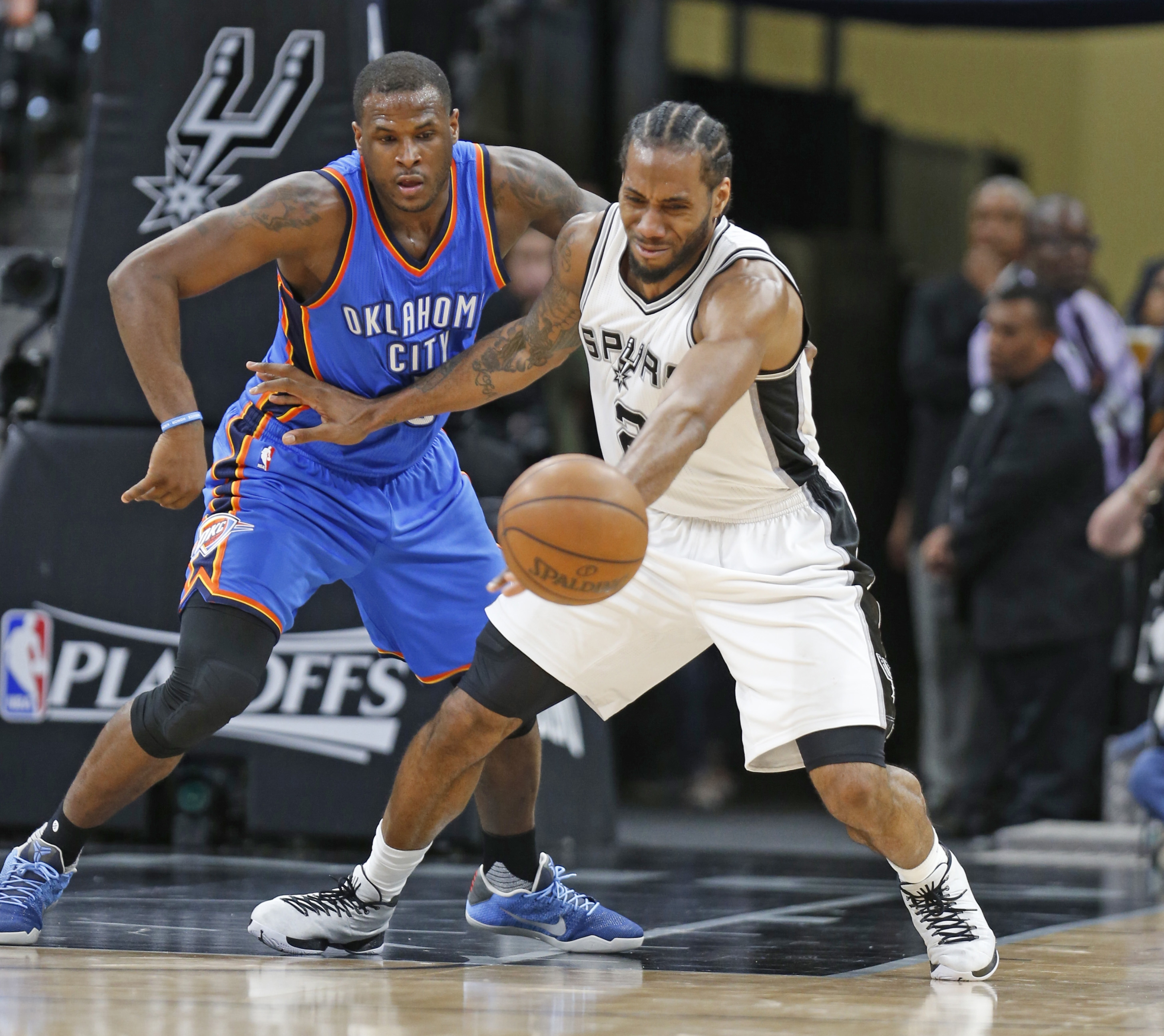 Kawhi Leonard of the San Antonio Spurs and Dion Waiters of the Oklahoma City Thunder go after the ball in Game Two of their Western Conference series Monday.