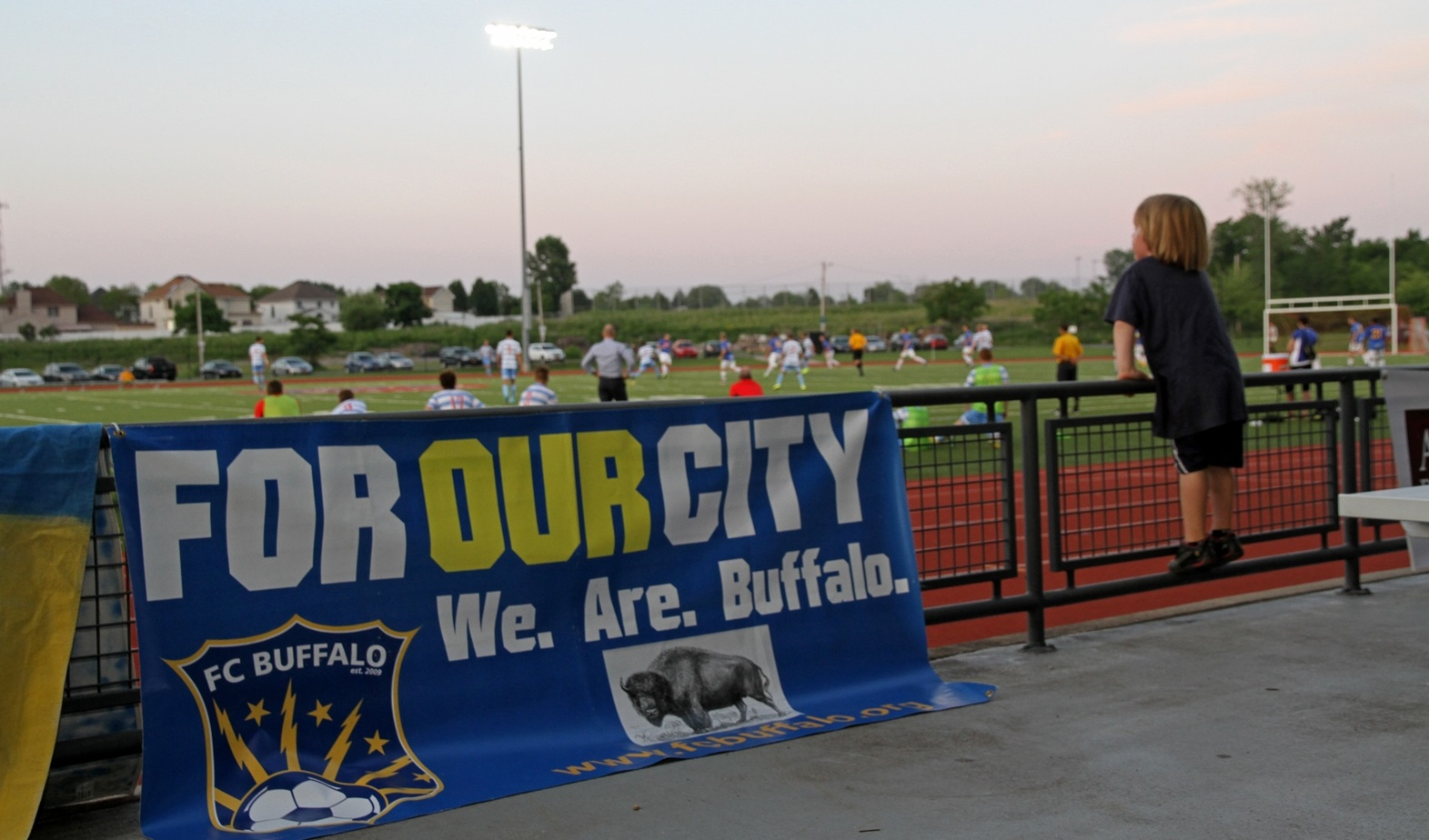 """A young fan watches an FC Buffalo match next to a club manner that sports the slogan """"For Our City."""" (Erica Malinowski/Special to The News)"""