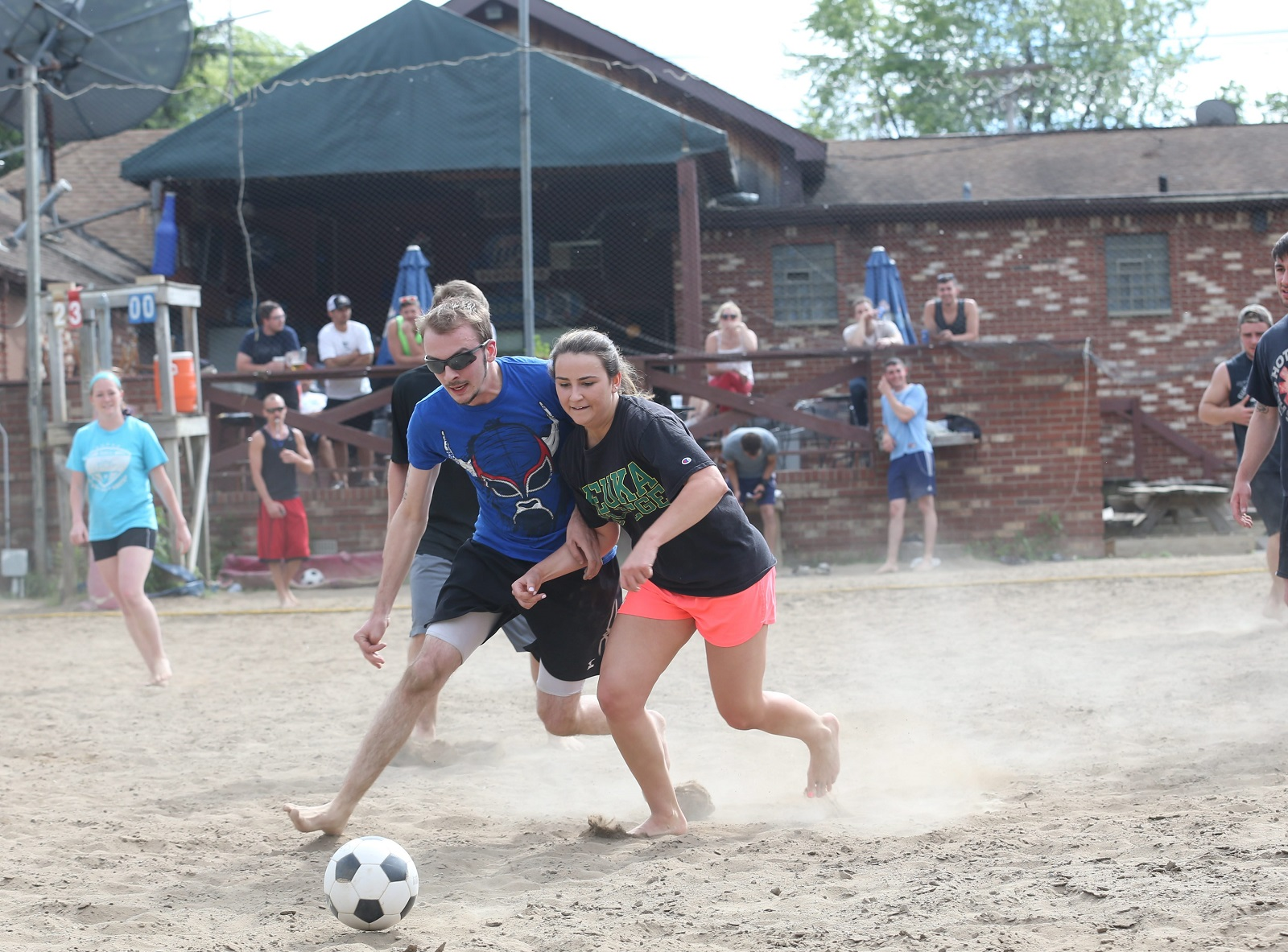 Flattery's at 1130 Orchard Park Road in West Seneca runs sand volleyball Monday through Friday nights and co-ed sand soccer on Sundays from 4 to 8 p.m. Opposing players Alex Will, left, and Lindsey Michaels go after a loose ball. (Sharon Cantillon/Buffalo News)