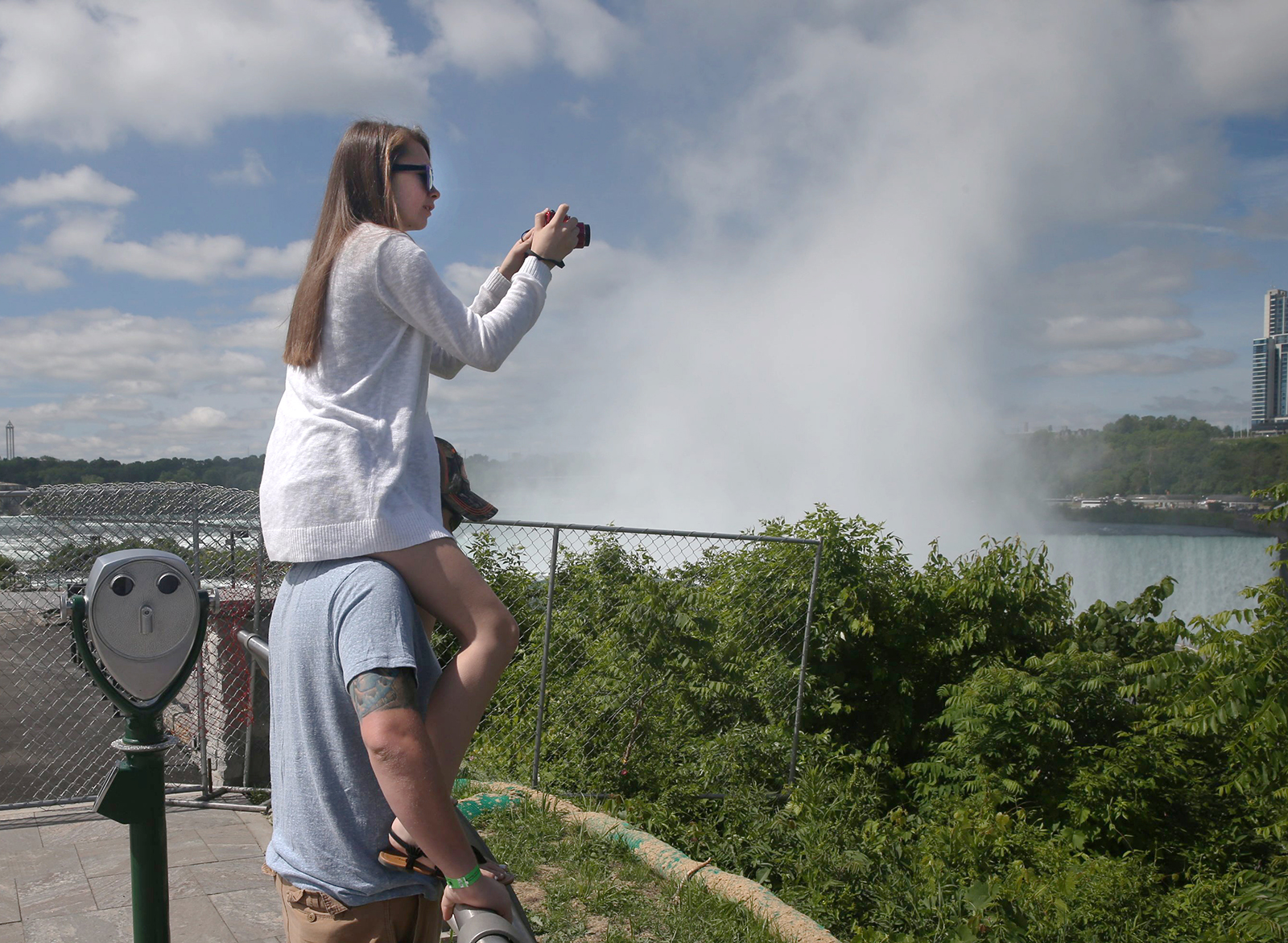 "Joslin Streck, of Oswego, N.Y. sits on the shoulders of her friend Quinn Hoko, of Blue Meadow, PA. to get a better photo at Niagara Falls State Park's Goat Island as construction fence keeps people out blocking views Terrapin Point and Horseshoe Falls, in Niagara Falls, N.Y., on Monday June 13, 2016. GPS Coordinates 43¼5'2"" N 79¼4'27"" W 550 ft Elevation, looking 226¼ W. (John Hickey/Buffalo News)"