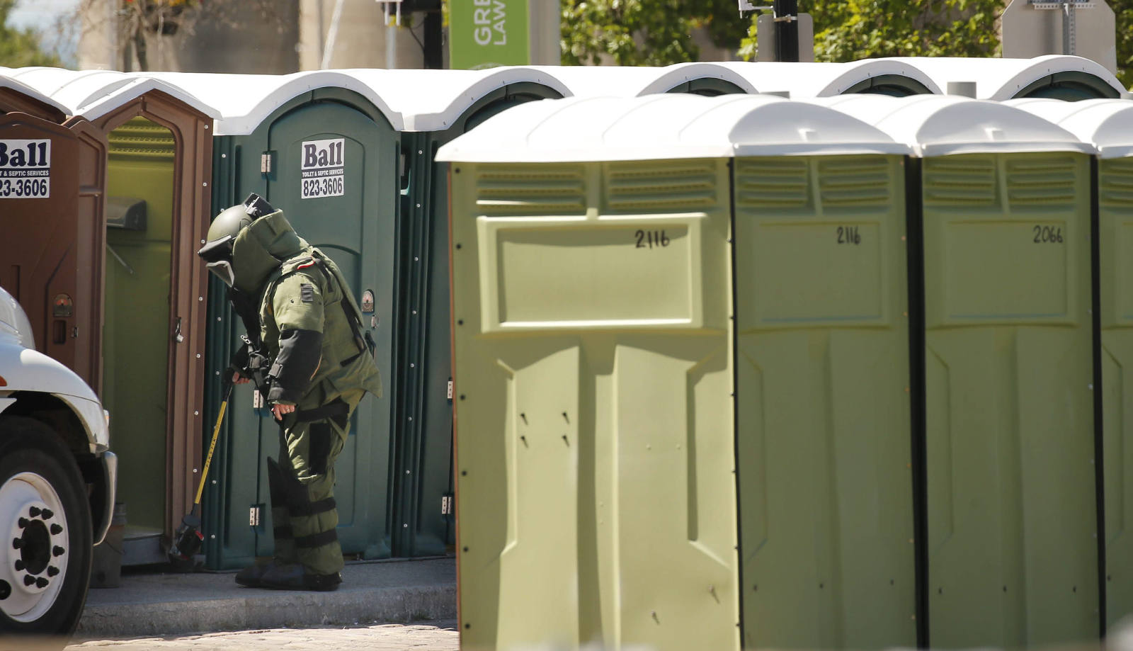 An Erie County Sheriff bomb technician examines a suspicious package in a portable toilet at Canalside, Friday, June 17, 2016. (Derek Gee/Buffalo News)