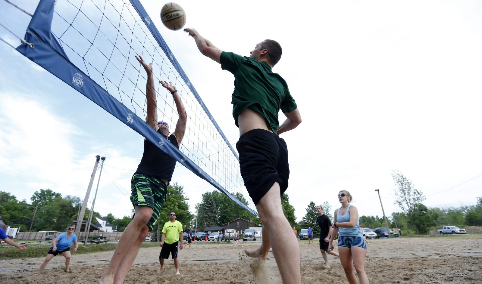 Members of the Buffalo Social Volleyball Club play a match on the sand courts at the Angry Buffalo at The Rose Garden in Williamsville. (Mark Mulville/Buffalo News)
