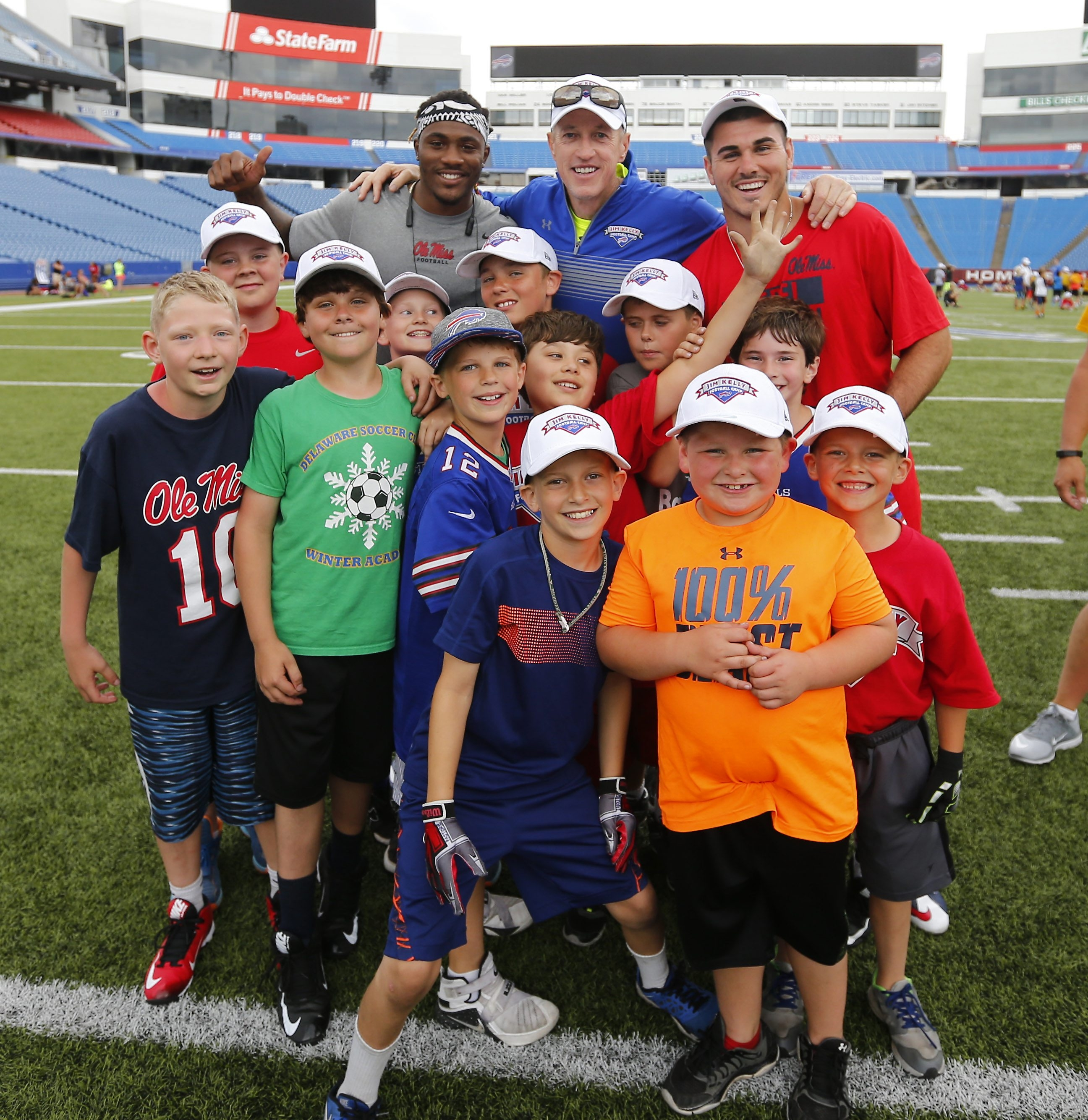 Top, from left, Mississippi receiver Damore'ea Stringfellow, Jim Kelly and Kelly's nephew, Mississippi quarterback Chad Kelly, pose with campers at Jim Kelly's annual football camp.