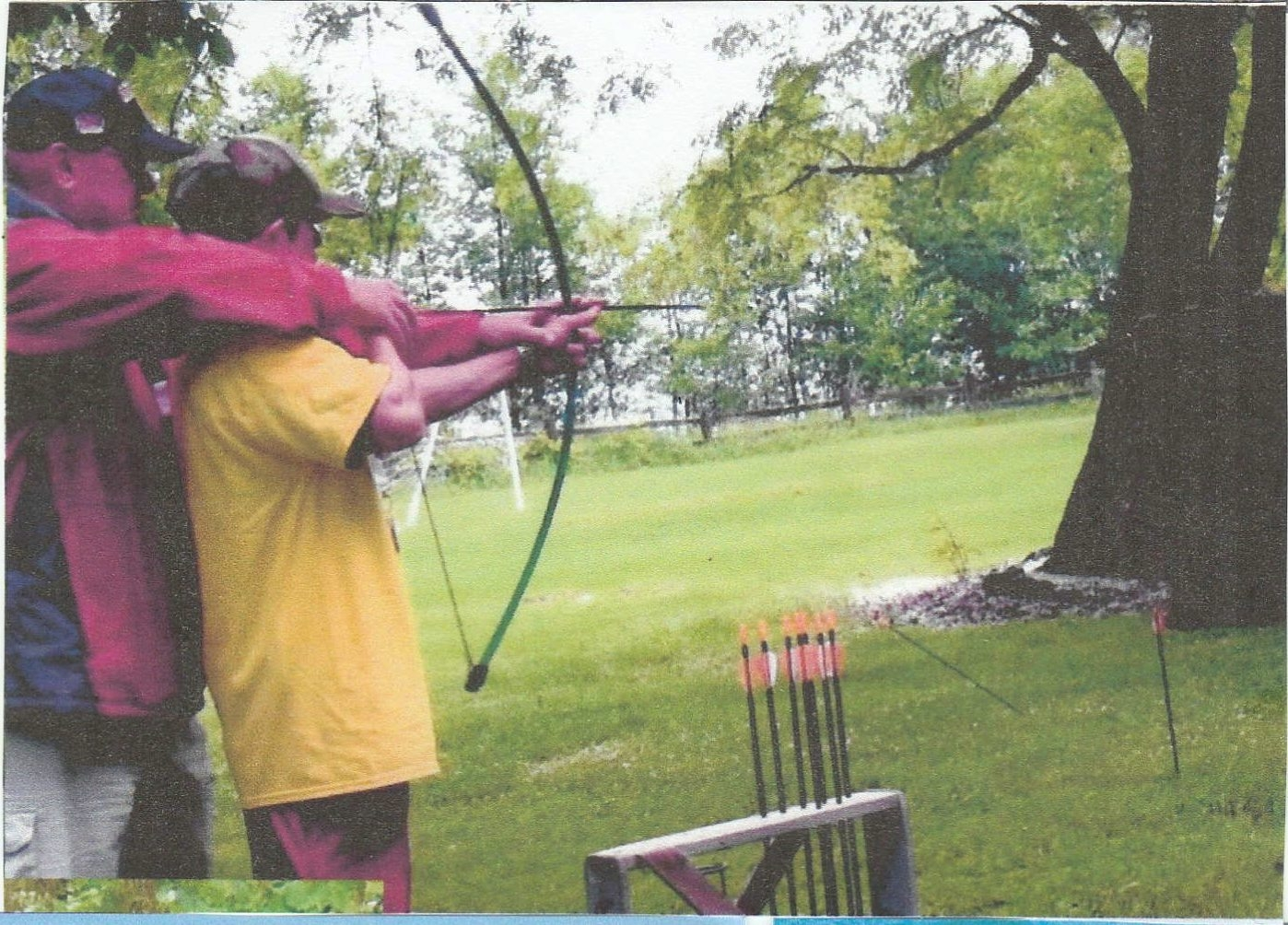 A volunteer gives an archery lesson to an unidentified camper at Niagara County Camp Happiness. A pig roast to benefit next year's camp will be held Aug 20 at the Lockport Elks Lodge.