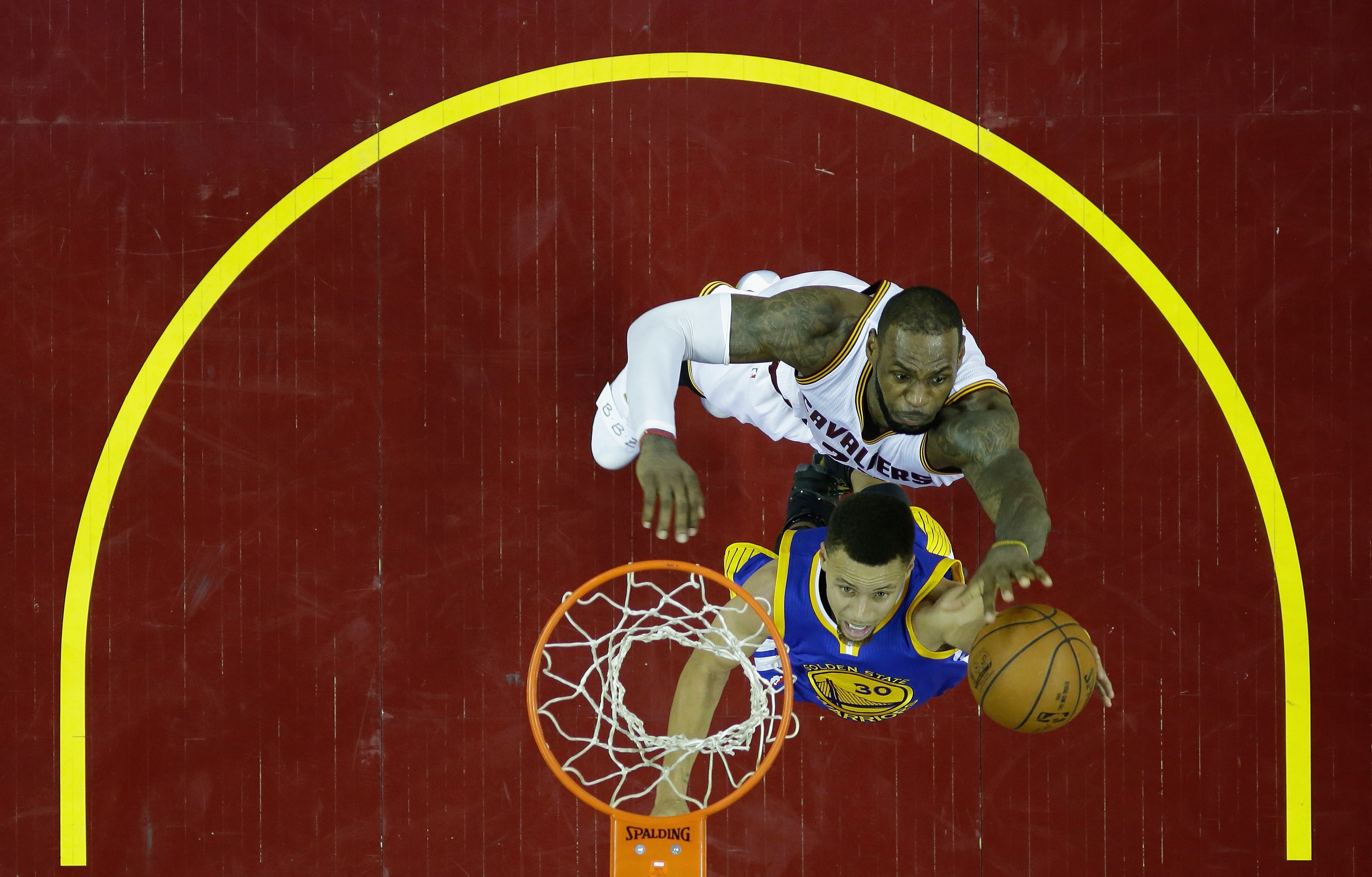 Stephen Curry drives to the basket as he is about to get blocked by LeBron James in Game Six of the 2016 NBA Finals.