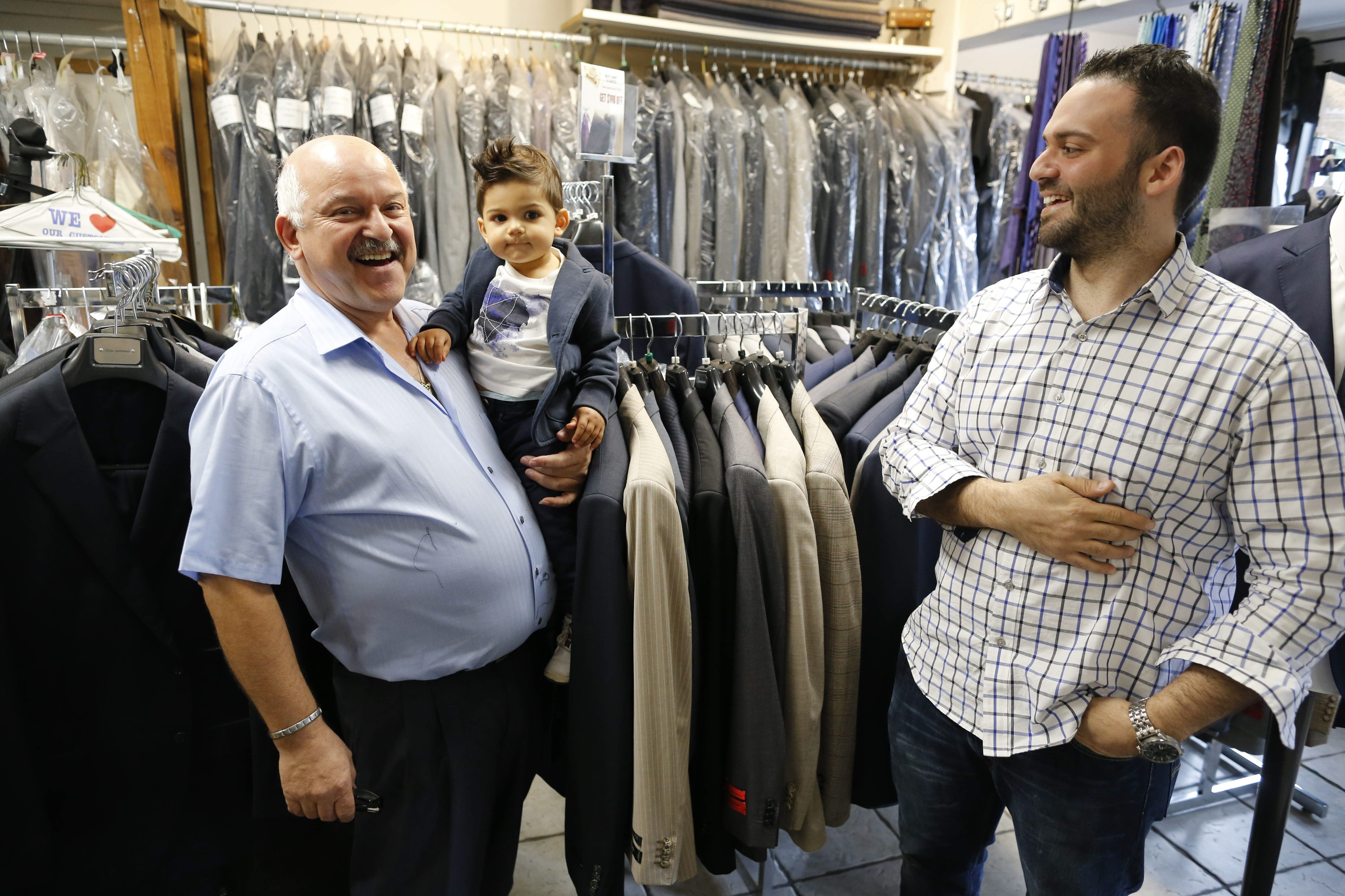 Gaetano Collana holds his 14-month-old grandson, Leonardo, while working in Tom & Luigi's Tailor Shop in West Seneca, which he runs with his son, Luigi, right.