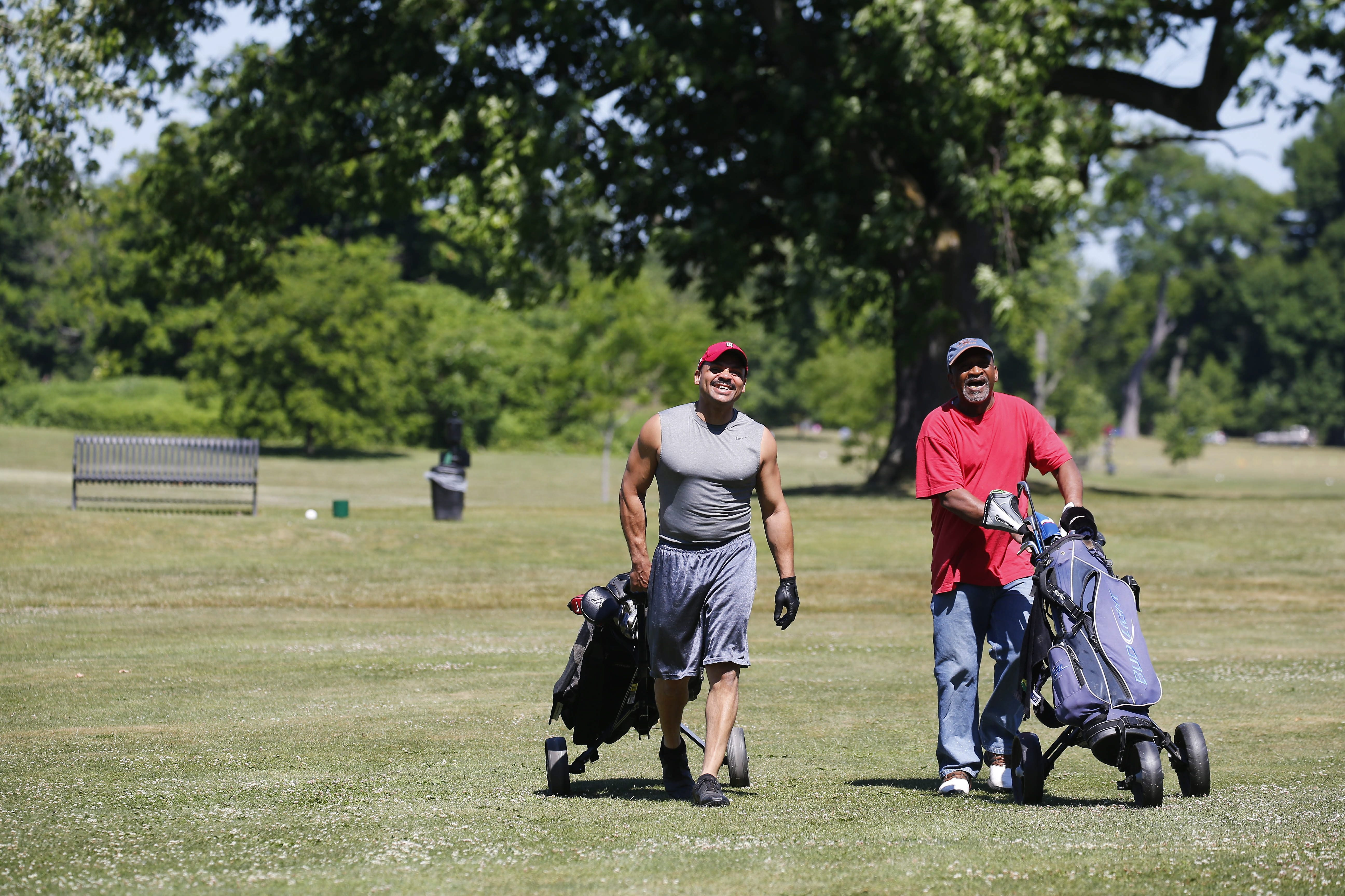 Ramon Suarez, left, and Bob Grice walk to their tee shots at the Delaware Park Golf course in Buffalo.