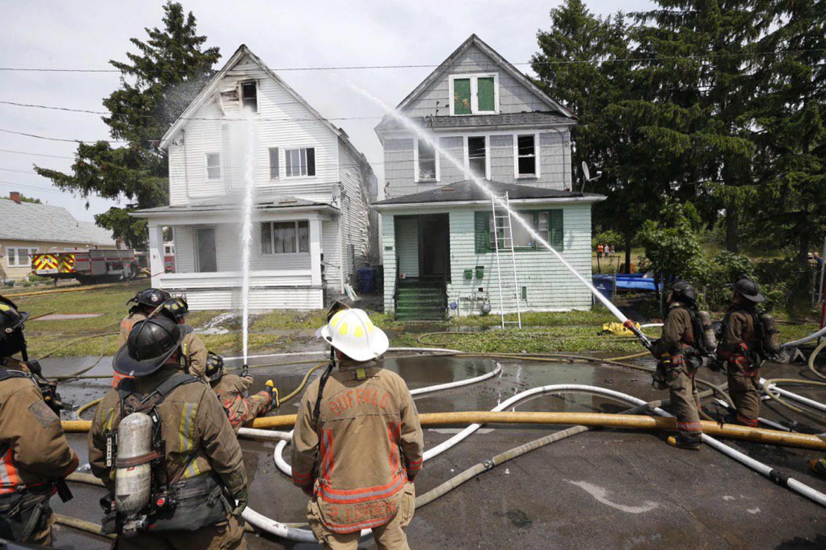 Firefighters battled a fire in two homes on Swinburne Street on Buffalo's East Side that spread due to high winds. (Derek Gee/Buffalo News)