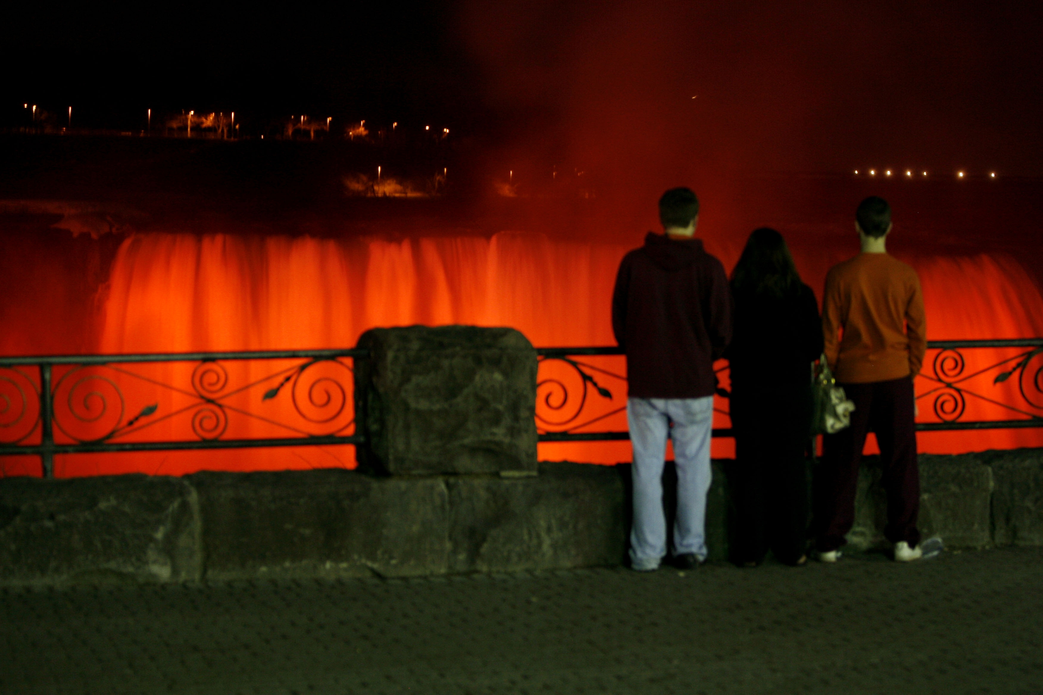 University at Buffalo students Tim Grant of Williamsville, left, Gina Grasta of Rochester and Chris Hodge of Union, N.J., watch as Niagara Falls is illuminated in red in 2007.