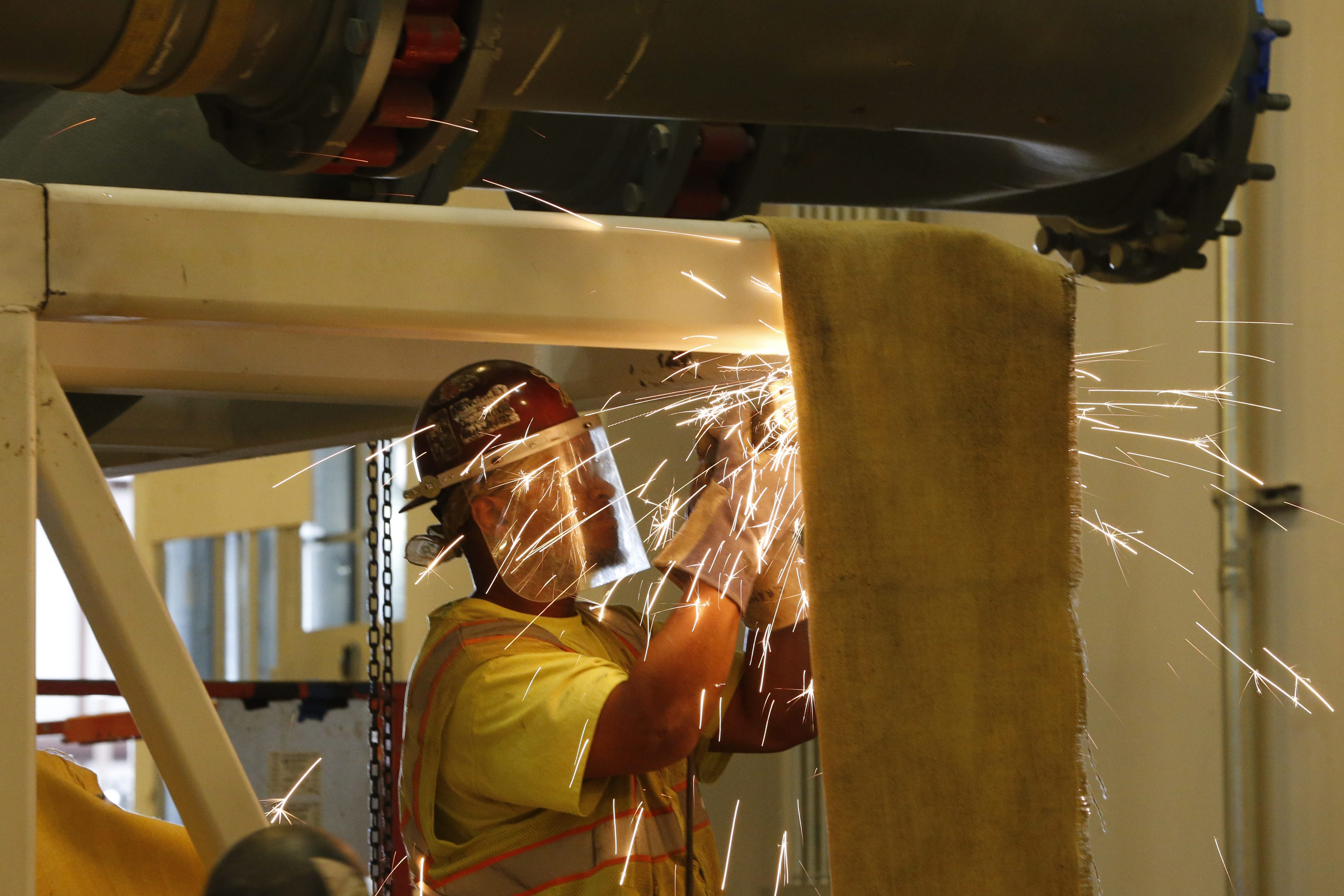 Sparks fly as a worker grinds the edges of a steel frame at the massive Solar City manufacturing facility at RiverBend.