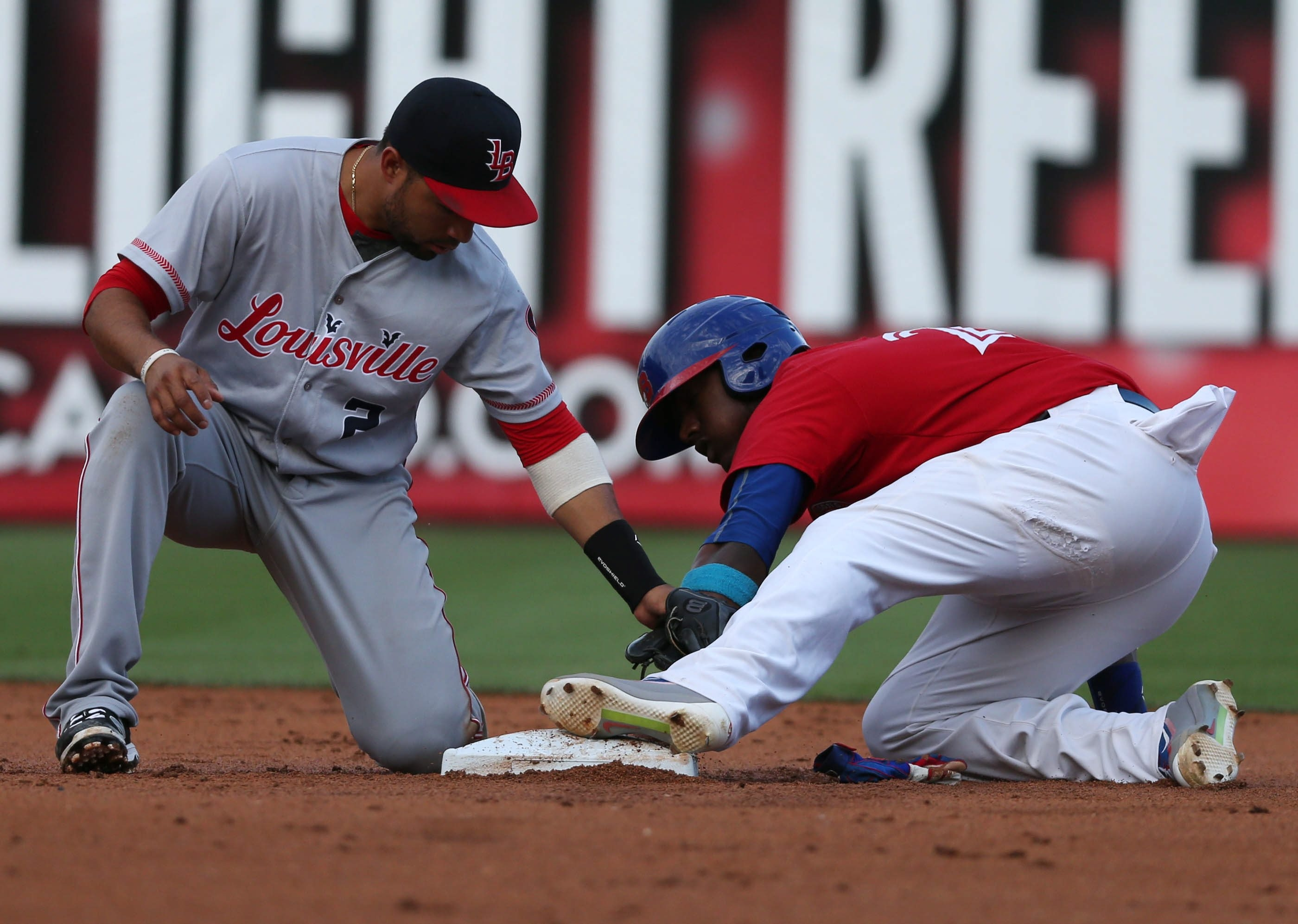 Junior Lake of the Bisons steals second, beating the tag by Louisville's Herman Iribarren in Wednesday night's game.