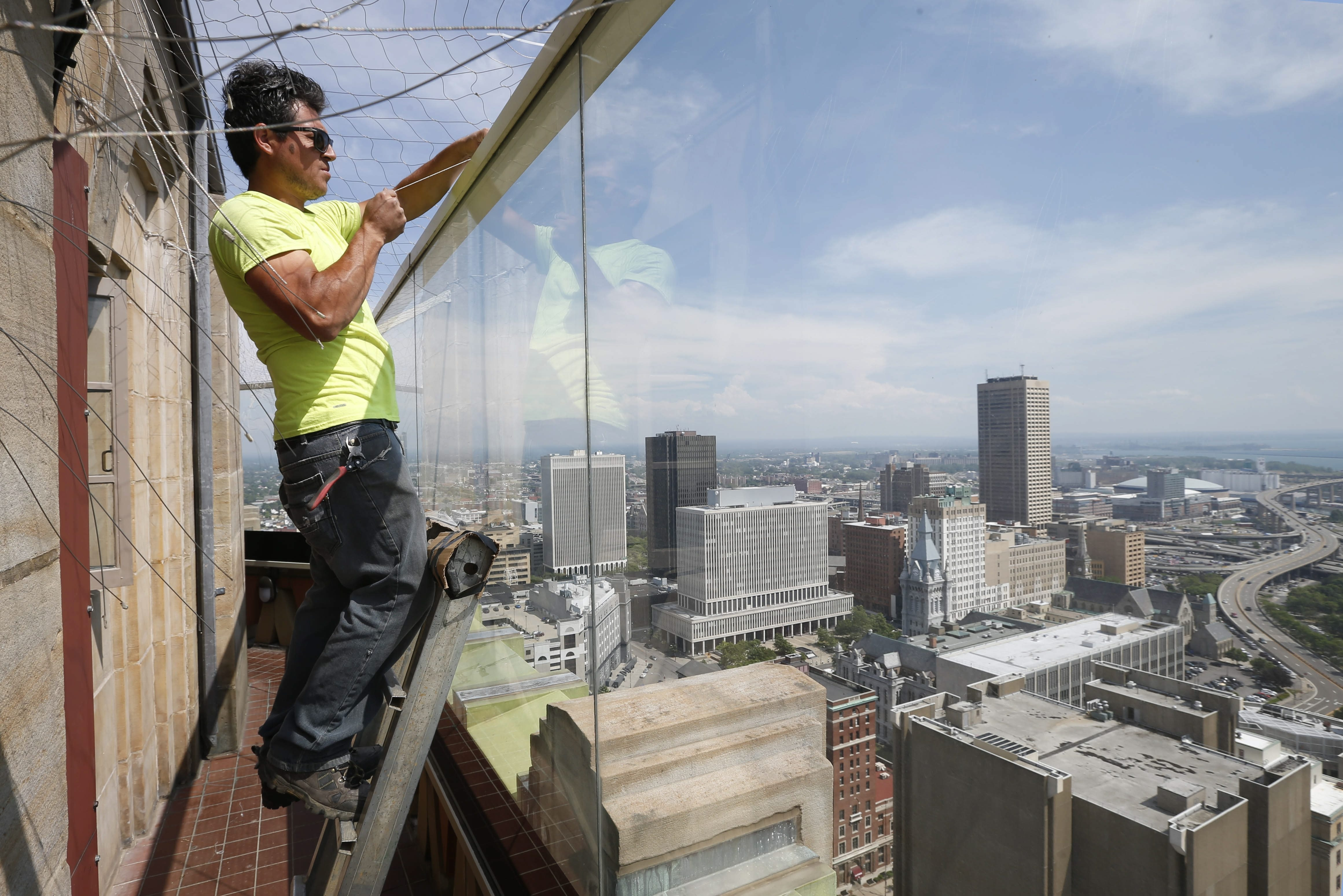 Andres Hernandez of Nets Unlimited installs a wire safety net over the outdoor observation deck on the 28th floor of Buffalo City Hall Monday.