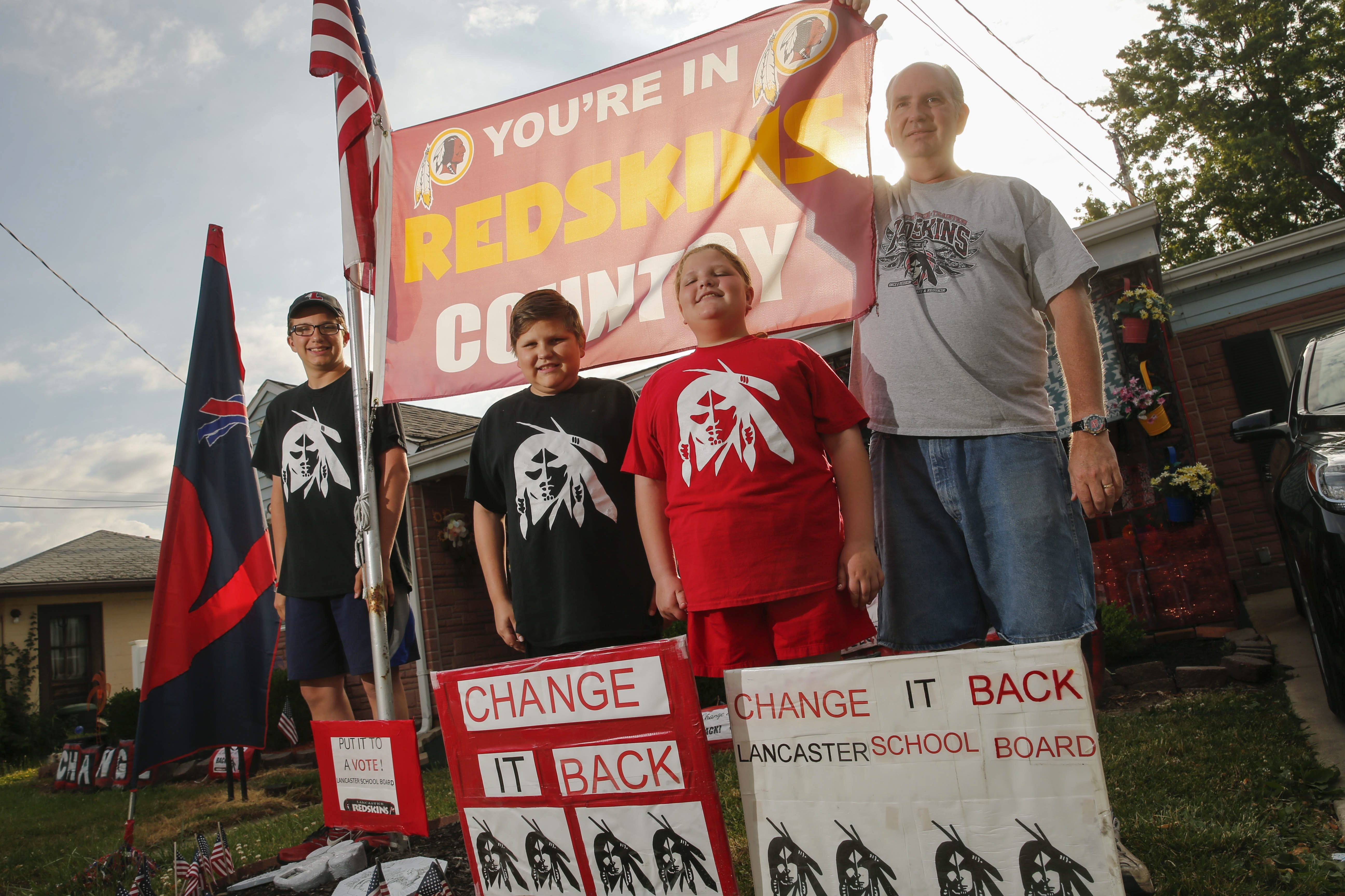 Dale Miller and his family, Dakota, 15, Blaze, 13, and Trinity, 11, want the Lancaster schools to return to the former mascot and have decorated their lawn in an effort to keep the issue alive. (Derek Gee/Buffalo News)
