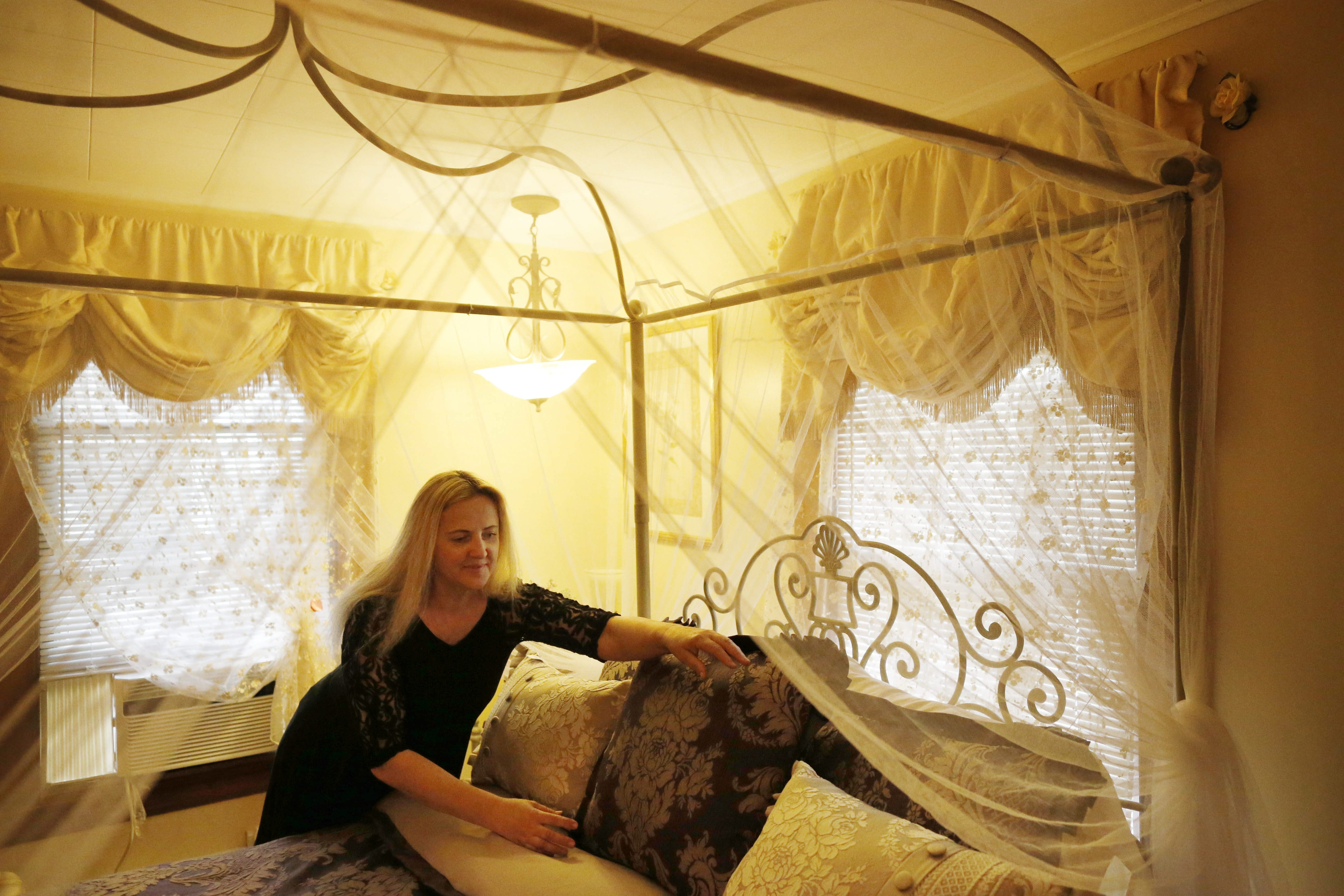 Halina Smouse, owner of the Butler House Bed and Breakfast, makes up a bed in a guest room. The Butler House is a fully licensed bed-and-breakfast, and takes a small percentage of its bookings from Airbnb. (Derek Gee/Buffalo News)