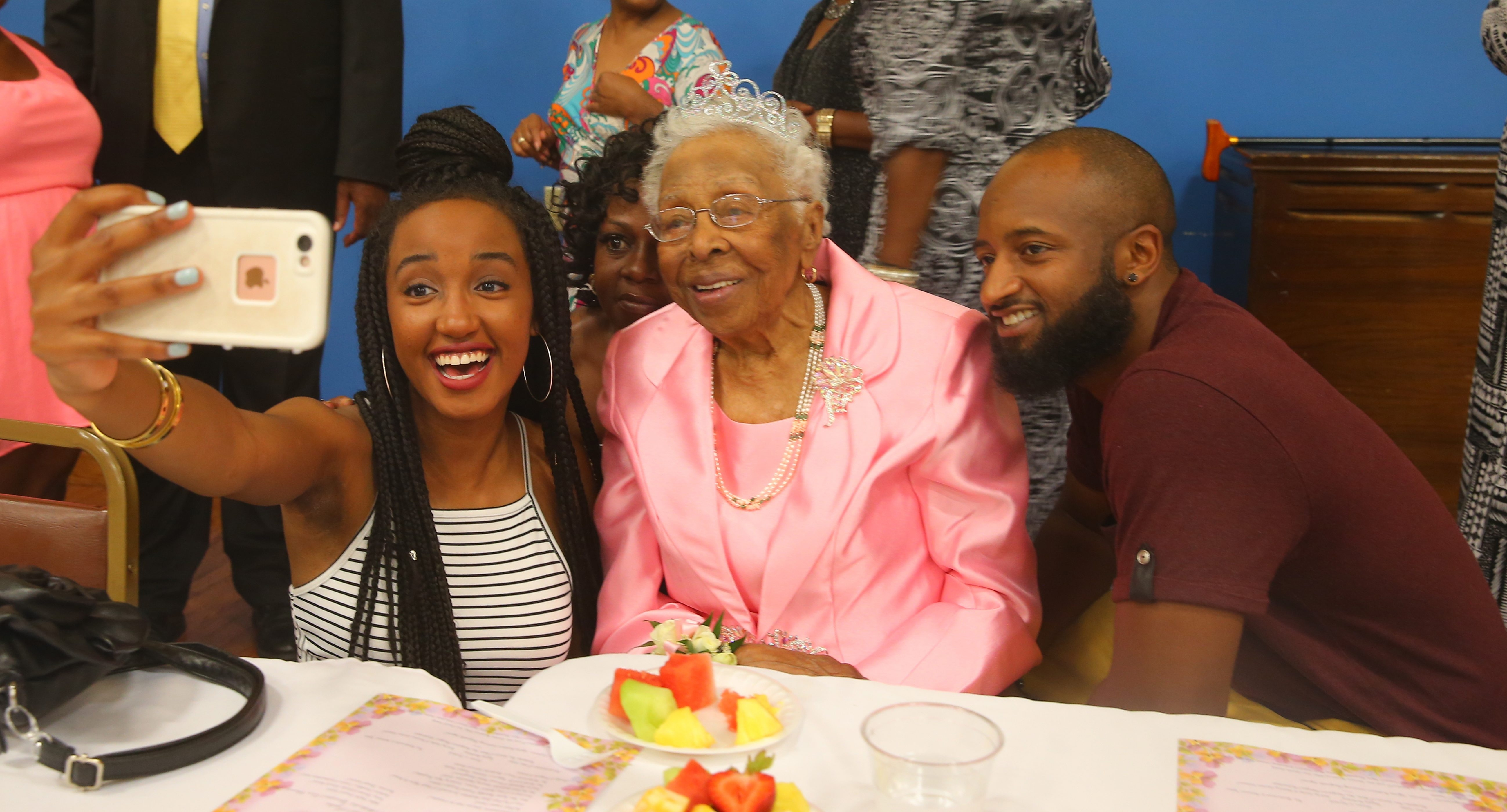 Margaret Richardson is the center of attention at her 100th birthday party as Chelsea Hall takes a selfie with Sonia Johnson, rear, and Tony Bryant at Durham Outreach Center.