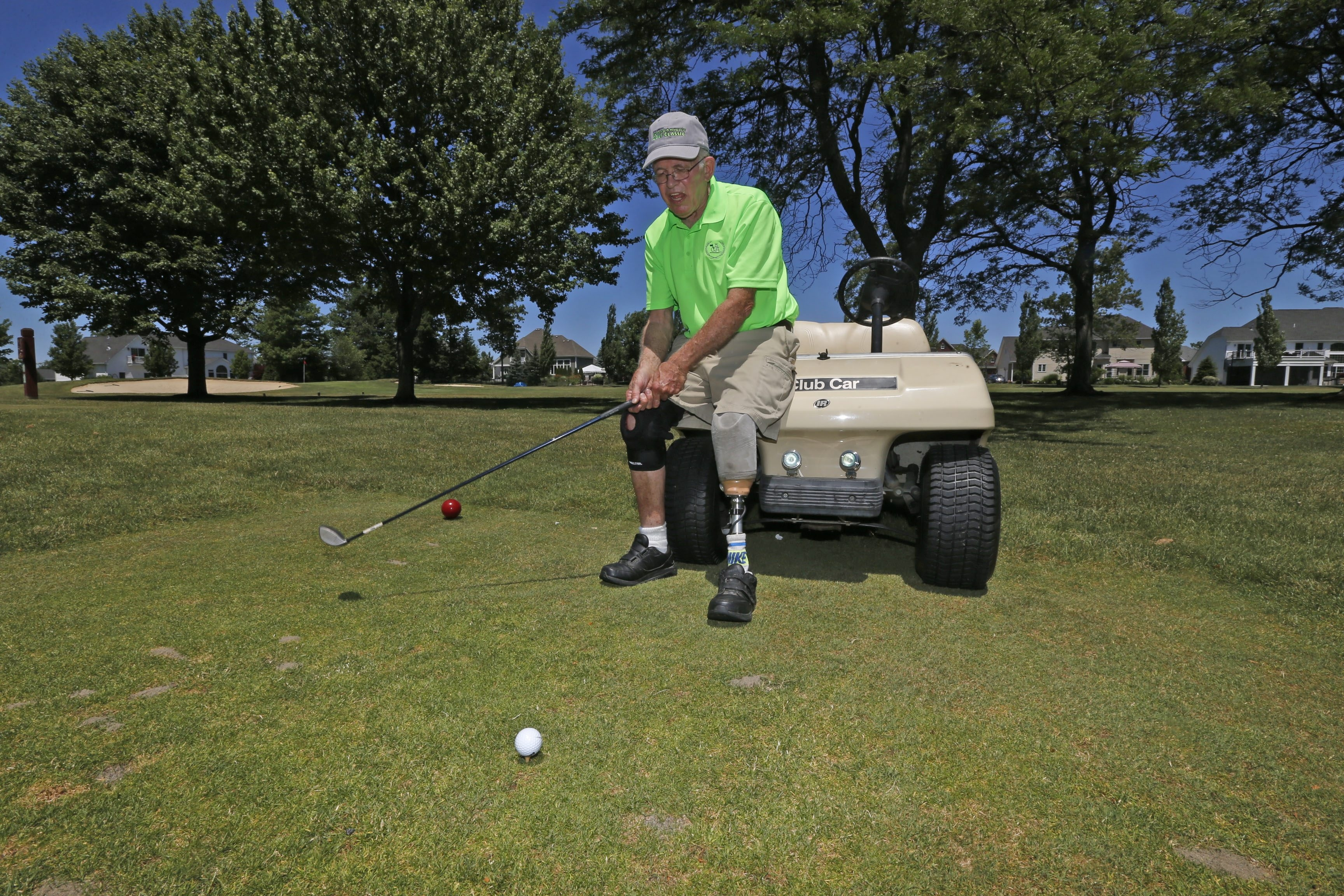 Tourney founder and past 19-year club pro Peter Fenn uses the front of his gold cart to stabilize himself as he tees off during the Eighth annual Buffalo Amputee Golf Classic on Monday at Brierwood Country Club.