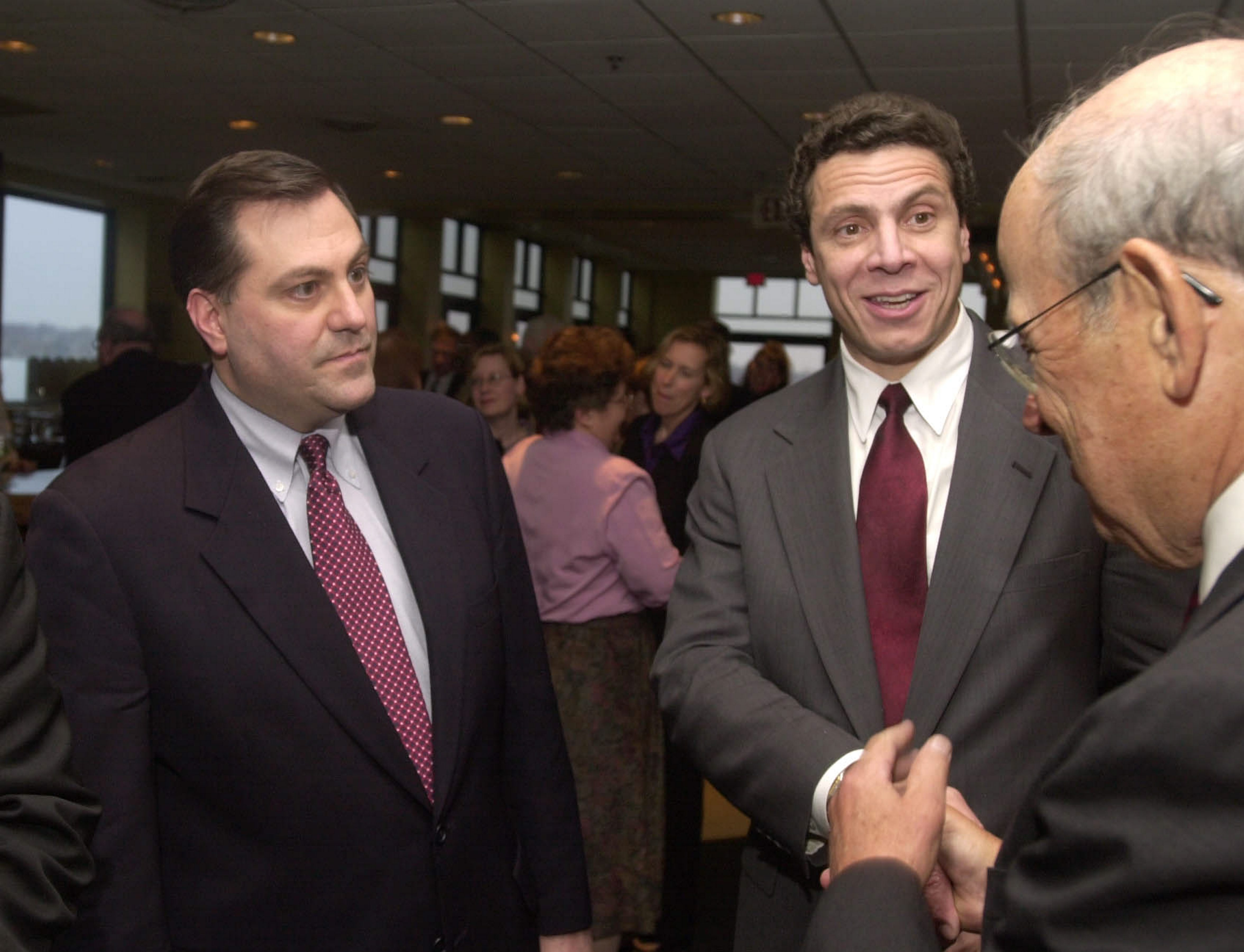 With local supporter G. Steven Pigeon at his side, Andrew M. Cuomo, then a first-time albeit unsuccessful Democratic candidate for governor, greets one of the attendees at Buffalo fundraising event in April 2002.