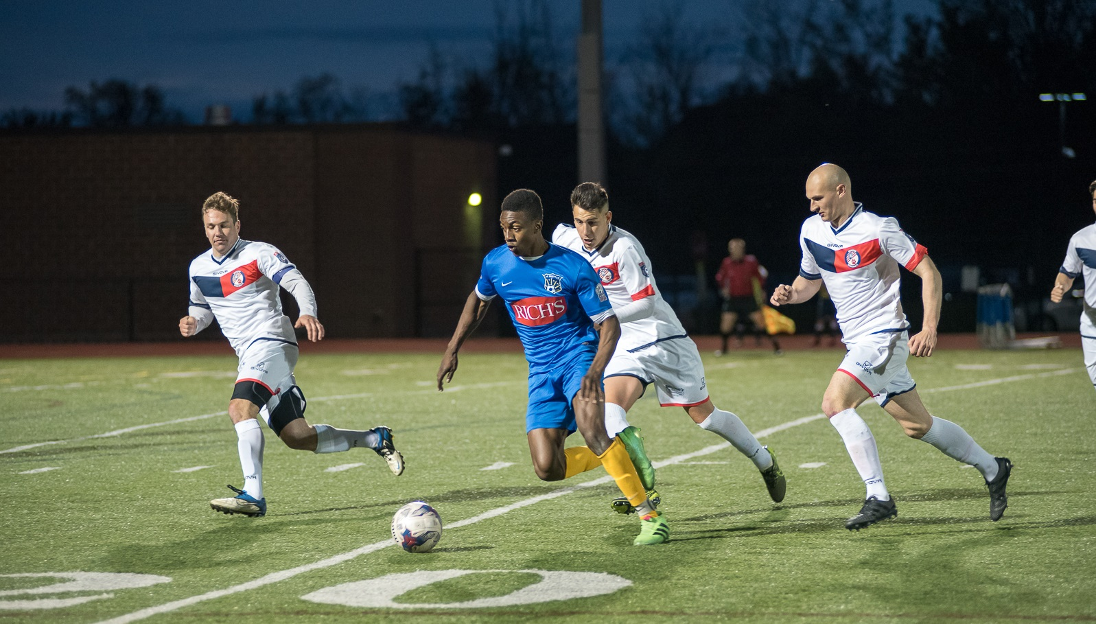 FC Buffalo's Isaiah Barrett, in blue, tries to elude three Rochester River Dogz defenders in the season opener. (Matt Weinberg/Special to The News)