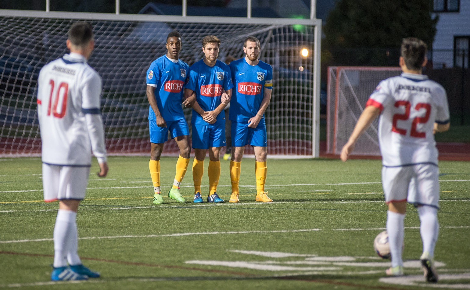 Isaiah Barrett, left in blue, eyes a Rochester free kick as part of FC Buffalo's wall. (Matt Weinberg/Special to The News)