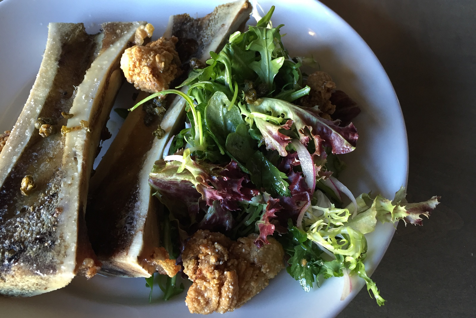 Fried capers and a lightly dressed salad offer pleasant counterbalance to unctuous bone marrow in this Thin Man starter. (Caitlin Hartney/Special to The News)