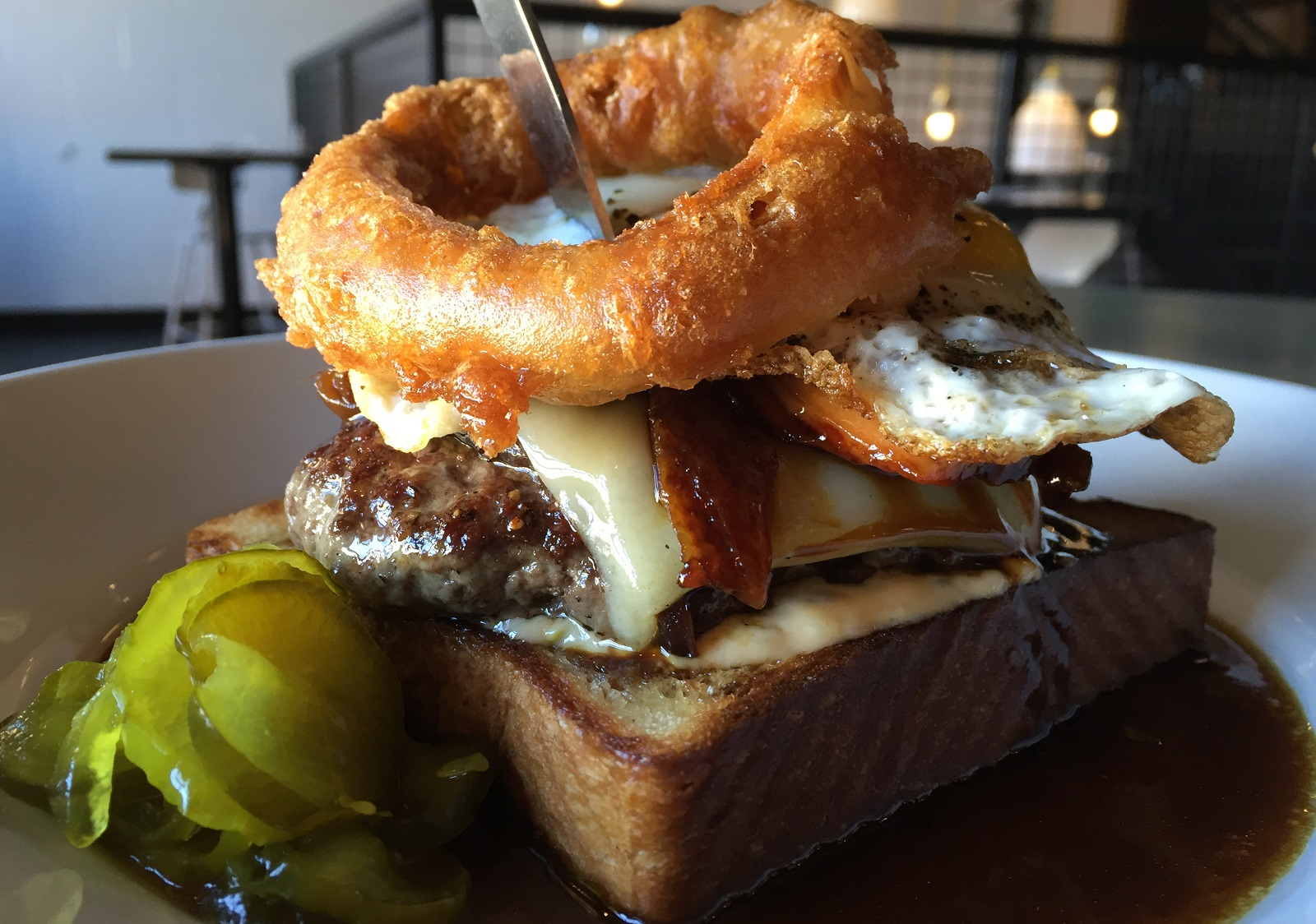 This open-faced, bone marrow burger comes piled with glazed pork belly, gruyere cheese, spicy remoulade, caramelized onions, fried egg, and an onion ring, for good measure. A thick slice of brioche serves as its indulgent foundation. (Caitlin Hartney/Special to The News)
