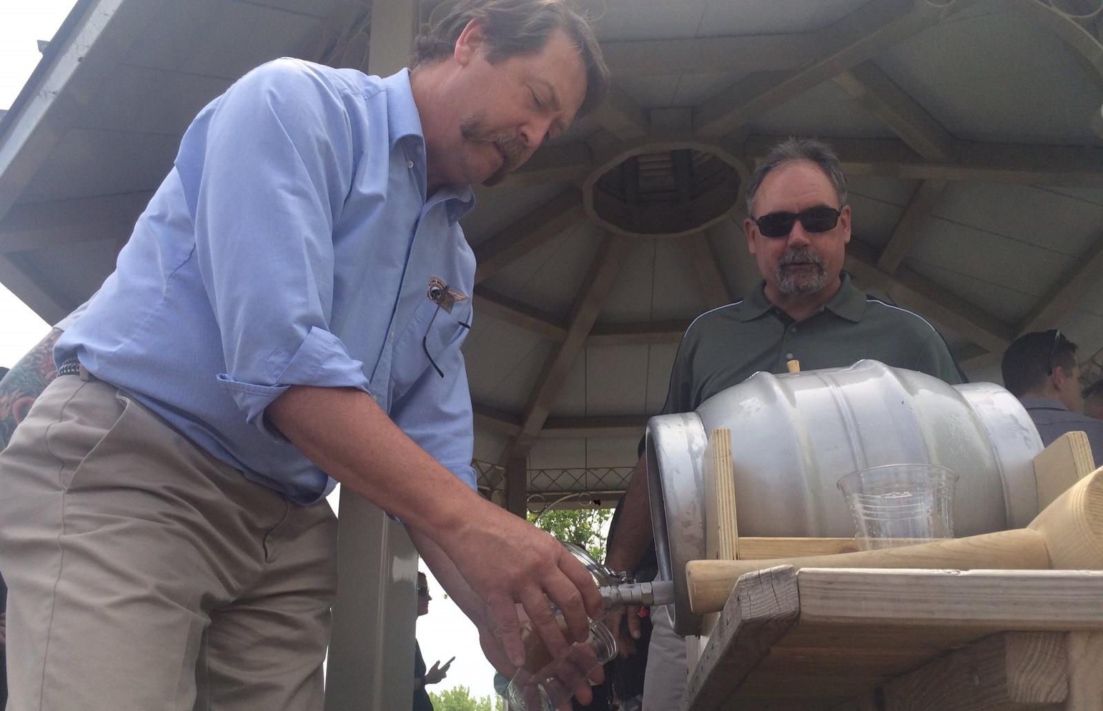 Flying Bison owner Tim Herzog, left, taps a mini keg of pale ale at the media gathering before the Buffalo Brewers Festival. (Alyssa Fisher/Buffalo News)