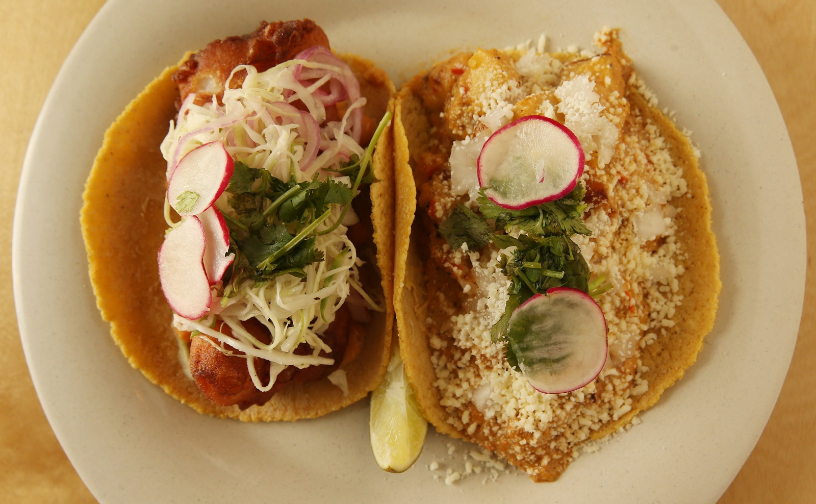 Deep South Taco's pescado taco, left, with crispy cod, chipotle mayo, cabbage, red onion; right, papas con rajas taco with potato, roasted poblano strips, chipotle, cotija cheese (Sharon Cantillon/Buffalo News)